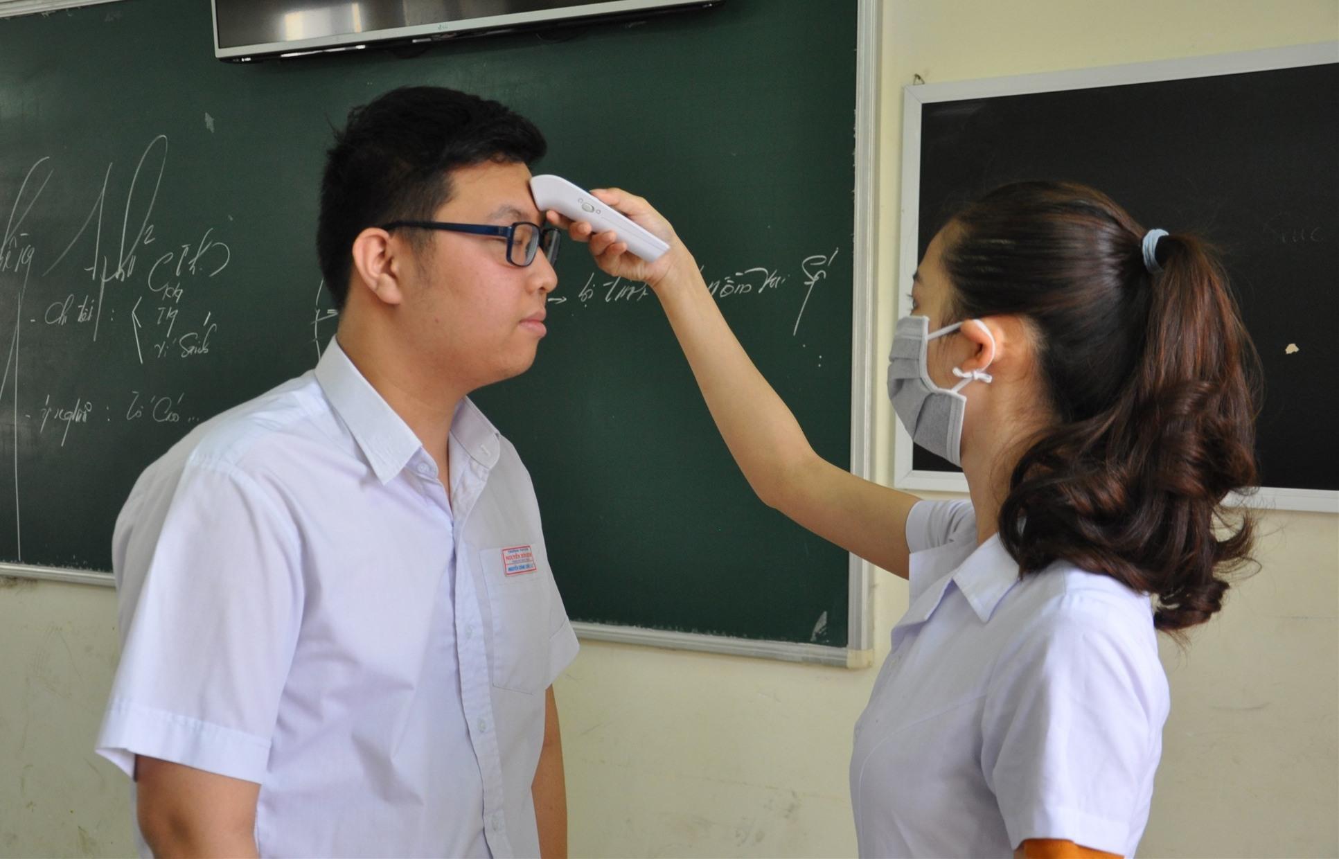 Đo thân nhiệt cho HS để sớm phát hiện trường hợp bị sốt nhằ phòng tránh nguy cơ dịch bệnh. Ảnh: X.P