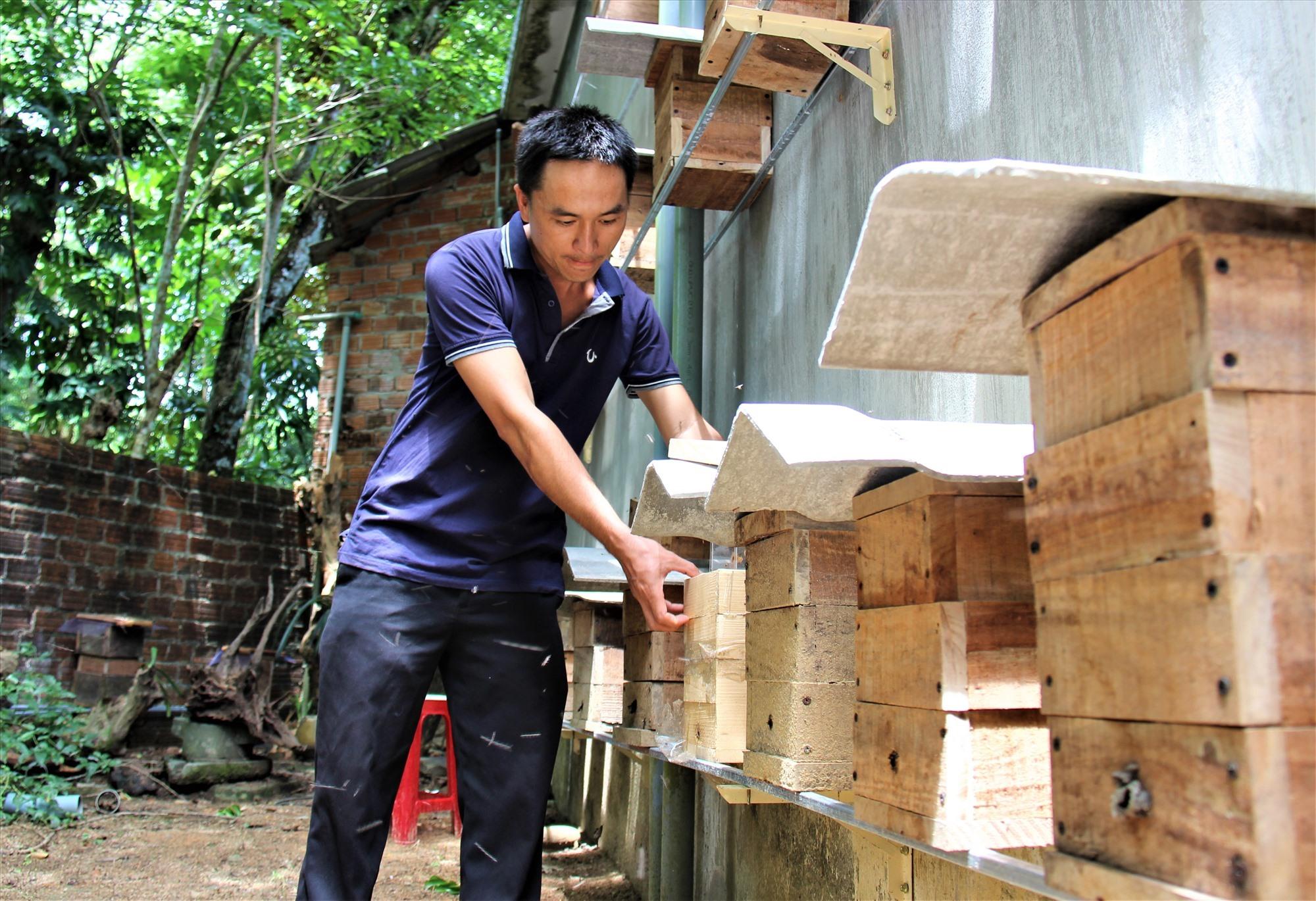 Anh Huỳnh Văn Trưởng chỉnh lại một số thùng ong dú. Ảnh: THANH THẮNG