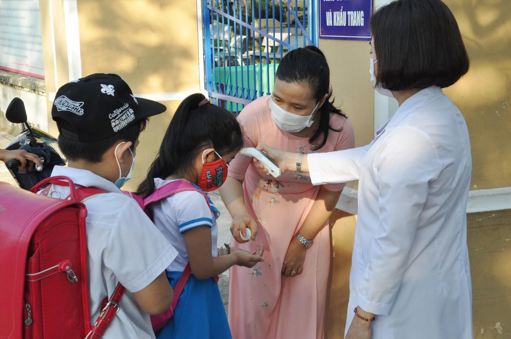 Trường Tiểu học Trần Quốc Toản (Tam Kỳ) tổ chức đo thân nhiệt và khử khuẩn cho HS từ hơn 6 giờ sáng tại cổng trường. Ảnh: X.P