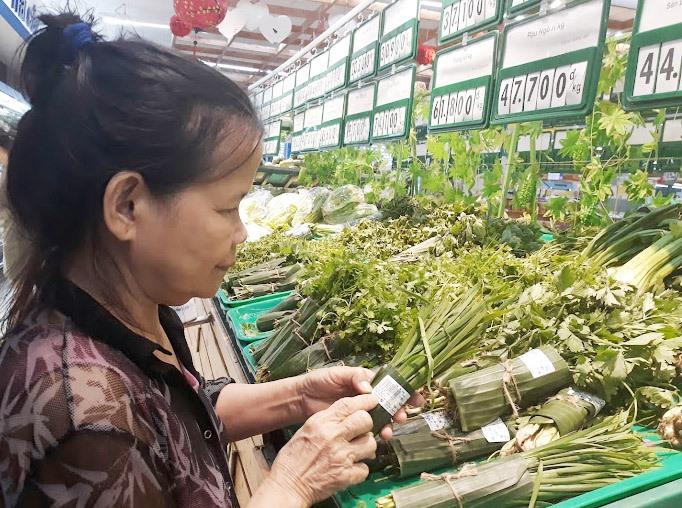 Khách hàng quan tâm sản phẩm gói bằng lá chuối ở siêu thị. Ảnh: C.N
