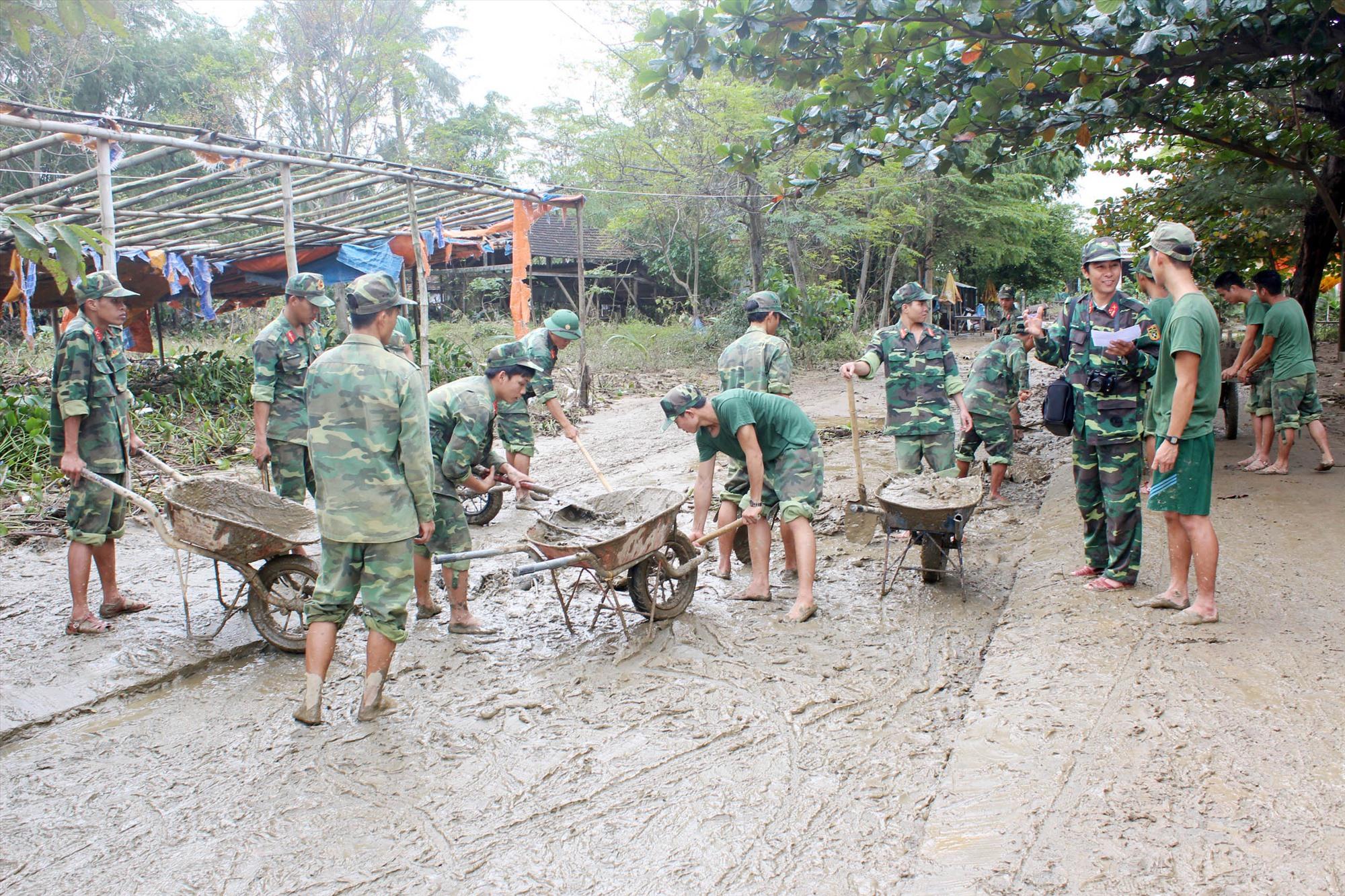 Cán bộ, chiến sĩ Trung đoàn 885 khắc phục hậu quả lũ lụt tại xã Cẩm Kim, TP.Hội An. Ảnh: TUẤN ANH