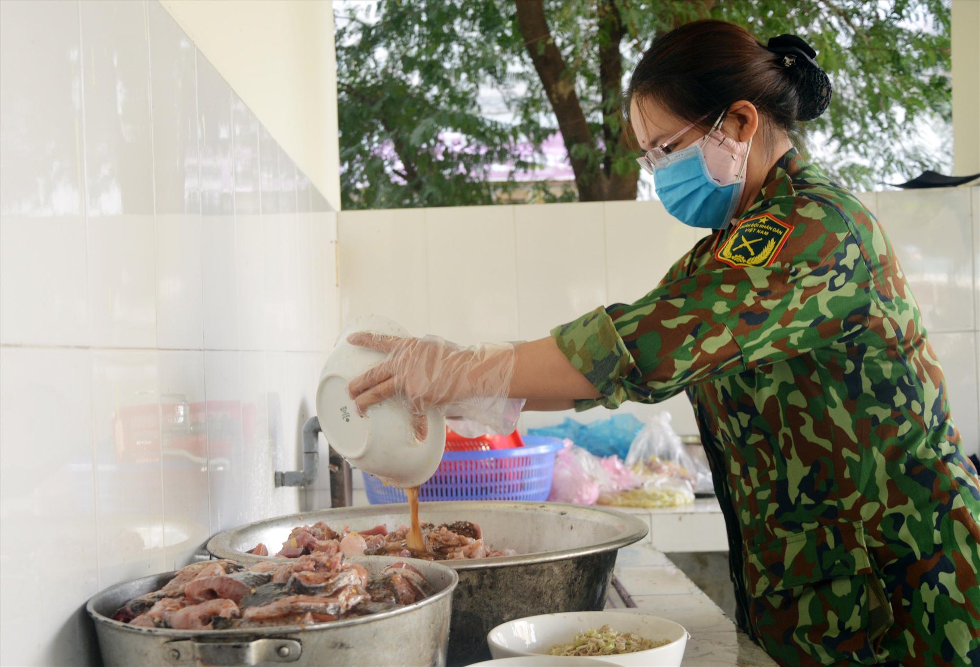 Chuẩn bị bữa ăn cho công dân tại khu cách ly tập trung. Ảnh: THÙY TRANG