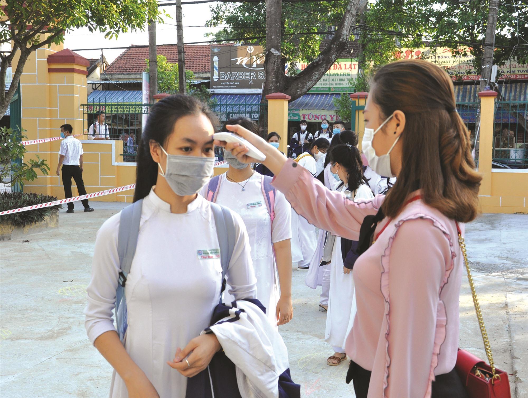 Trường THPT Phan Bội Châu (Tam Kỳ) thực hiện đo thân nhiệt cho học sinh trước khi vào lớp. Ảnh: X.P