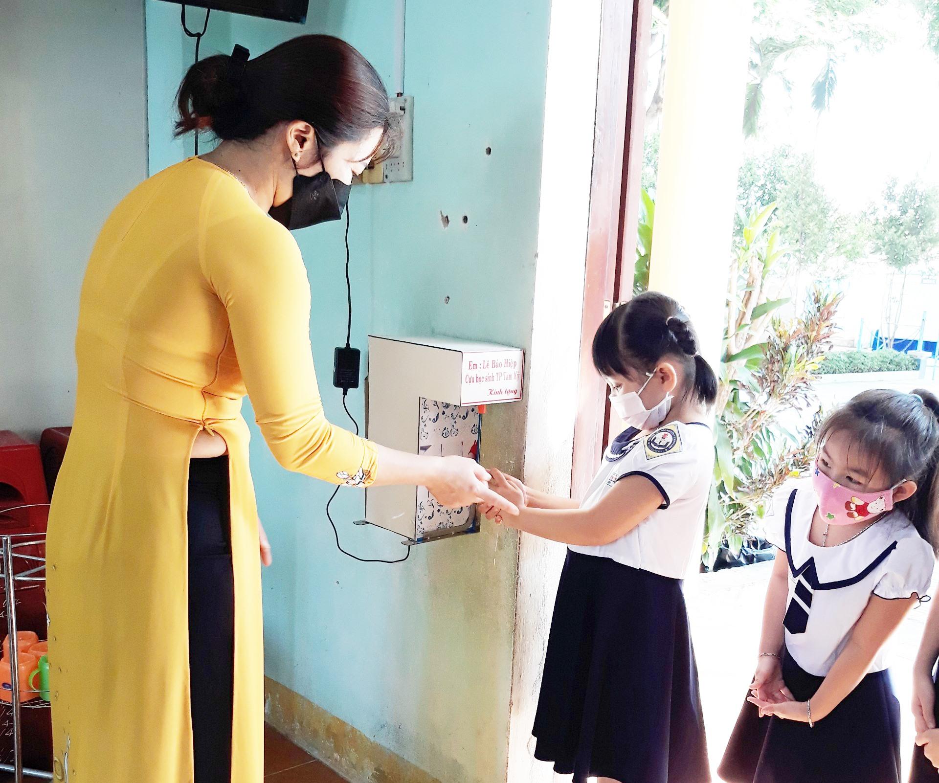 Học sinh lớp 1 Trường Tiểu học Nguyễn Thị Minh Khai (Tam Kỳ) sử dụng máy rửa tay cảm ứng do Lê Bảo Hiệp tặng. Ảnh: G.V
