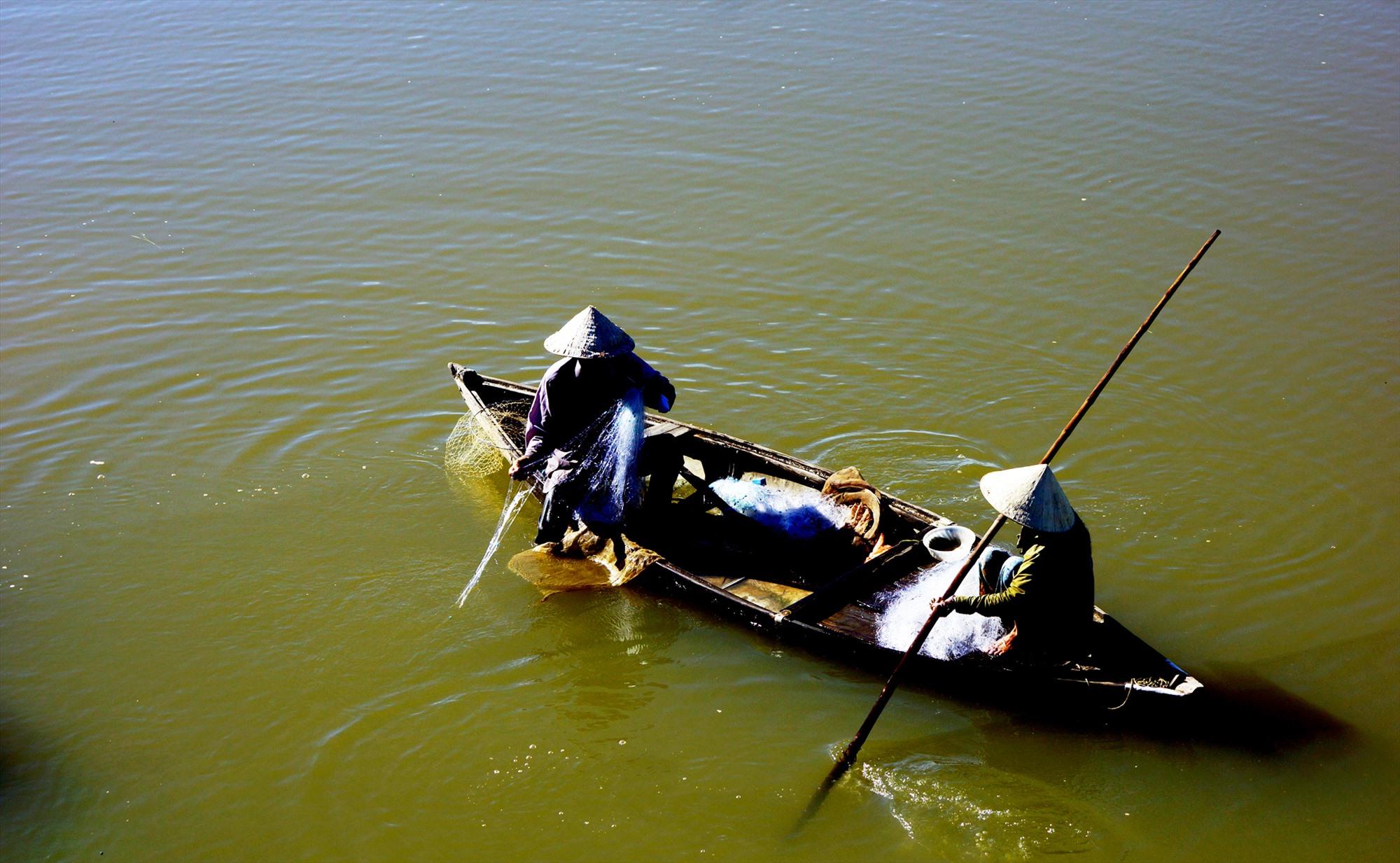 Thả lưới bắt cá trên sông. Ảnh: PHƯƠNG THẢO