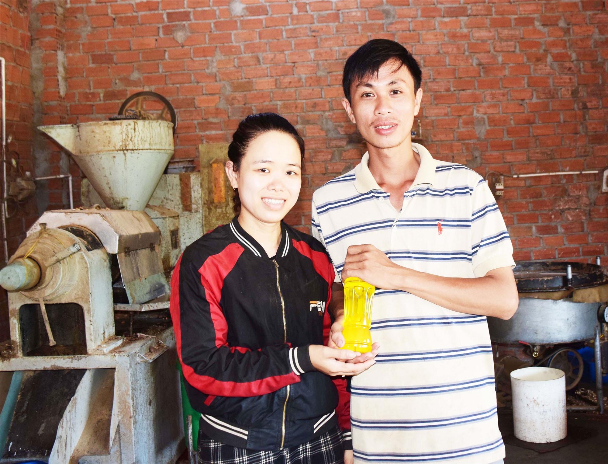 Vợ chồng anh Nguyễn Văn Lâm với sản phẩm dầu được cho ra từ chiếc máy ép công nghiệp đầu tiên của xã. Ảnh: THÁI CƯỜNG