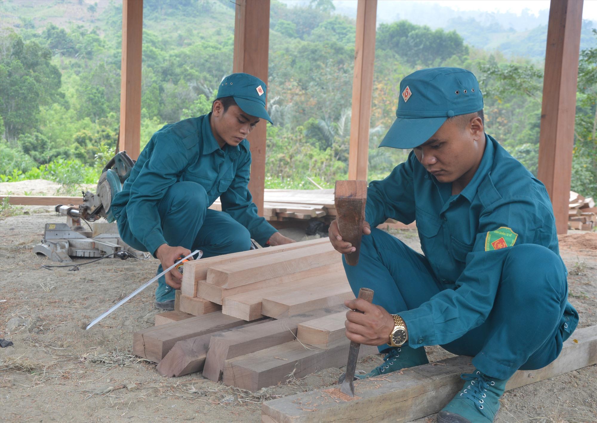 Lực lượng DQTT xã Đắc Pring giúp dân dựng nhà ở. Ảnh: A.T