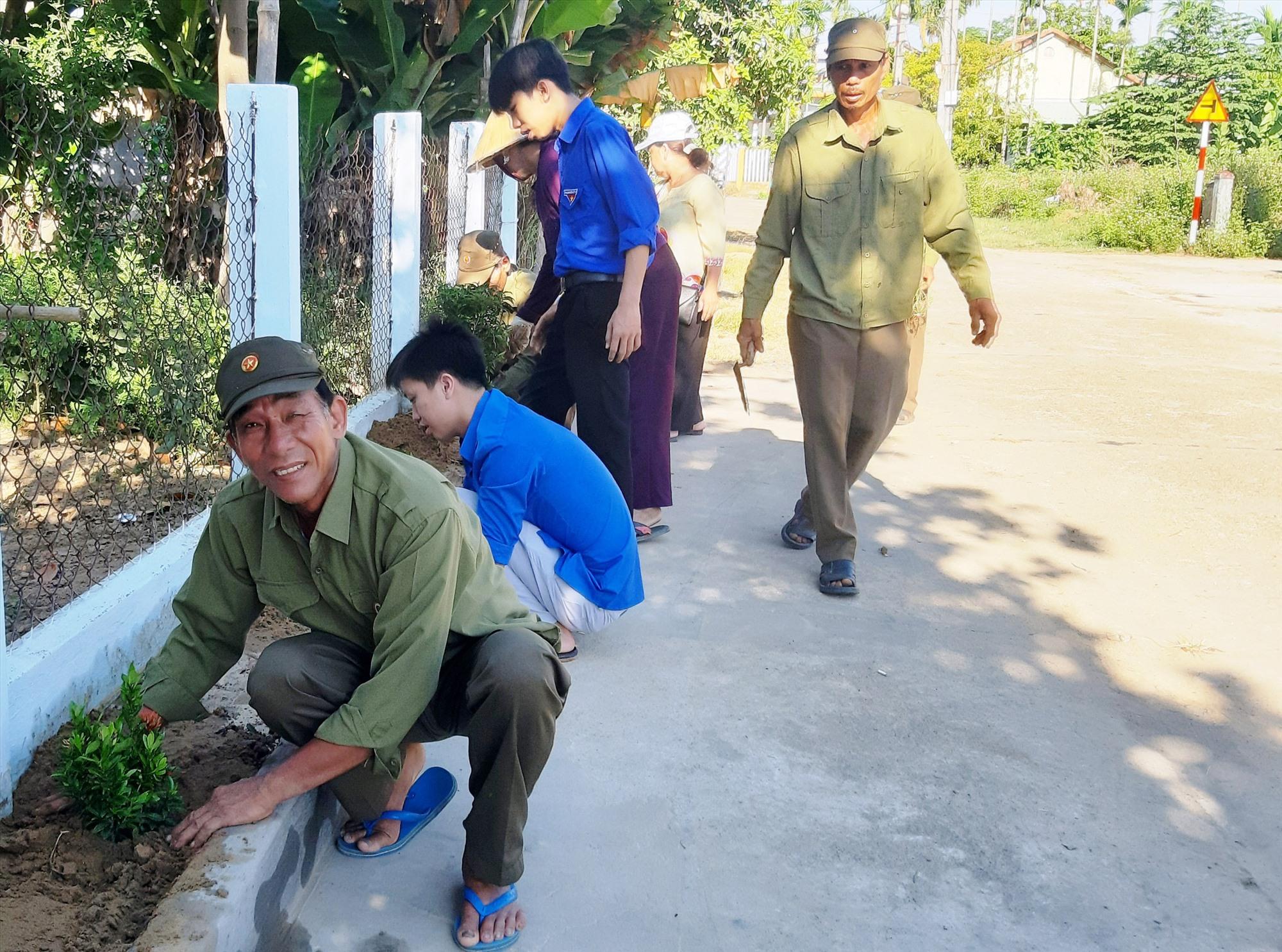 Đoàn viên, hội viên và người dân thôn Phú Bông (Duy Trinh, Duy Xuyên) ra quân trồng hoa dọc theo trục đường chính. Ảnh: L.T