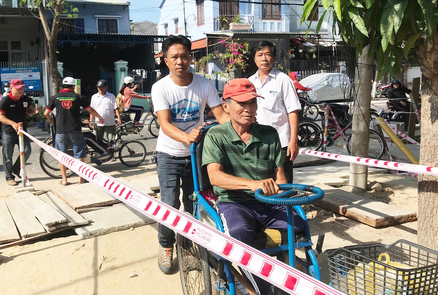 Hỗ trợ người dân khi đến nhận gạo.