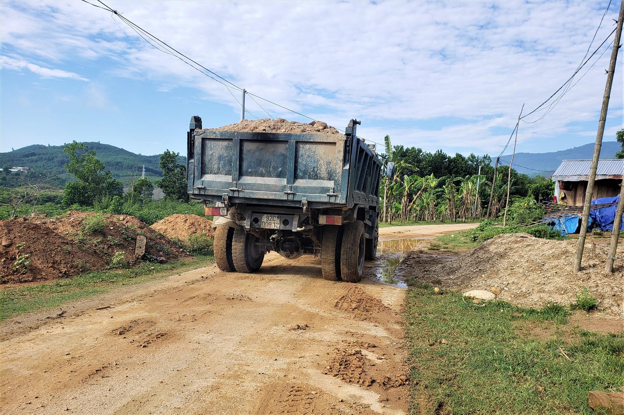 Xe tải chở không đậy kín khiến đất rơi vãi xuống đường qua xã Phước Gia (Hiệp Đức). Ảnh: THANH THẮNG