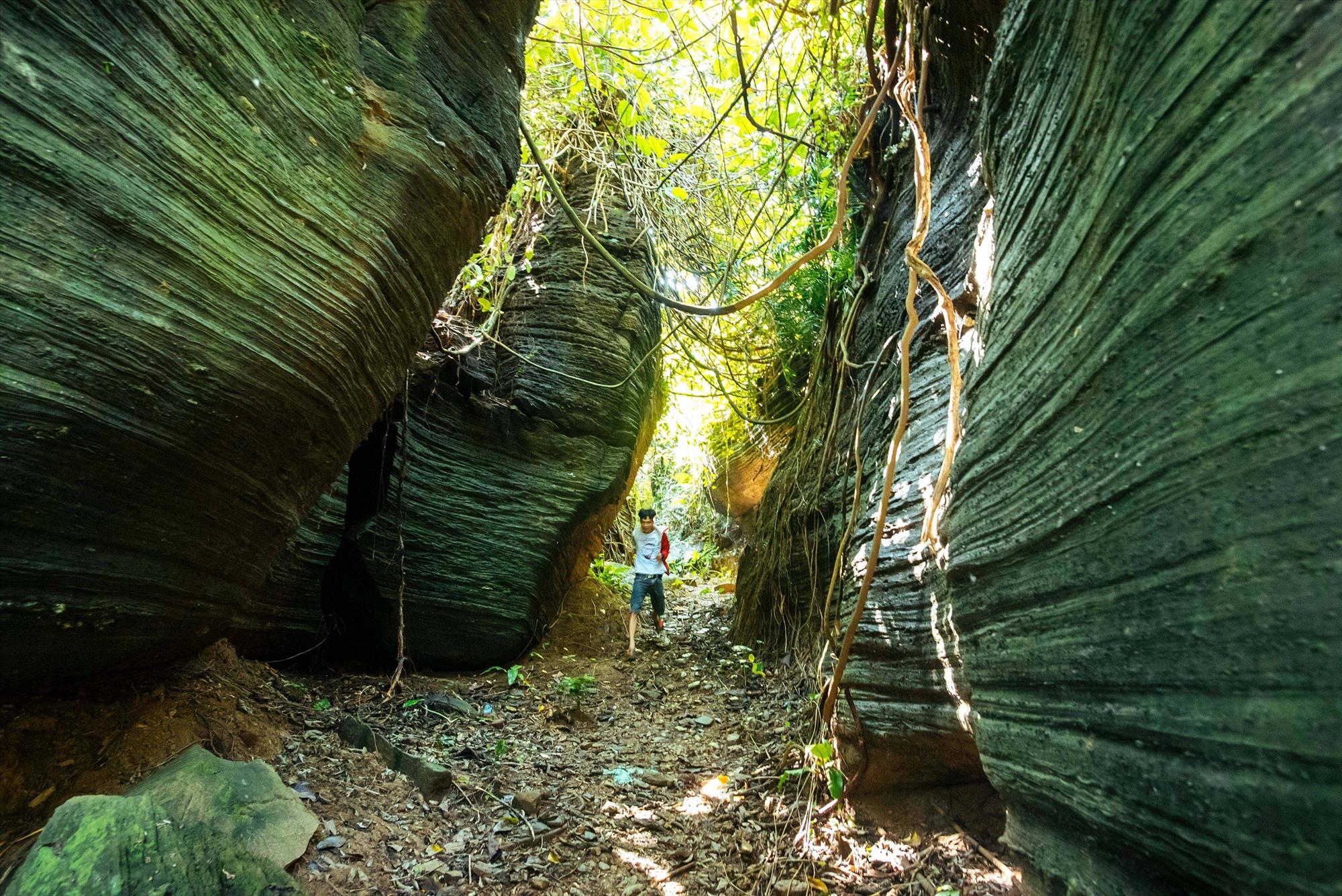 Đường vào hang vách đá dựng những hình thù và màu sắc kỳ ảo.