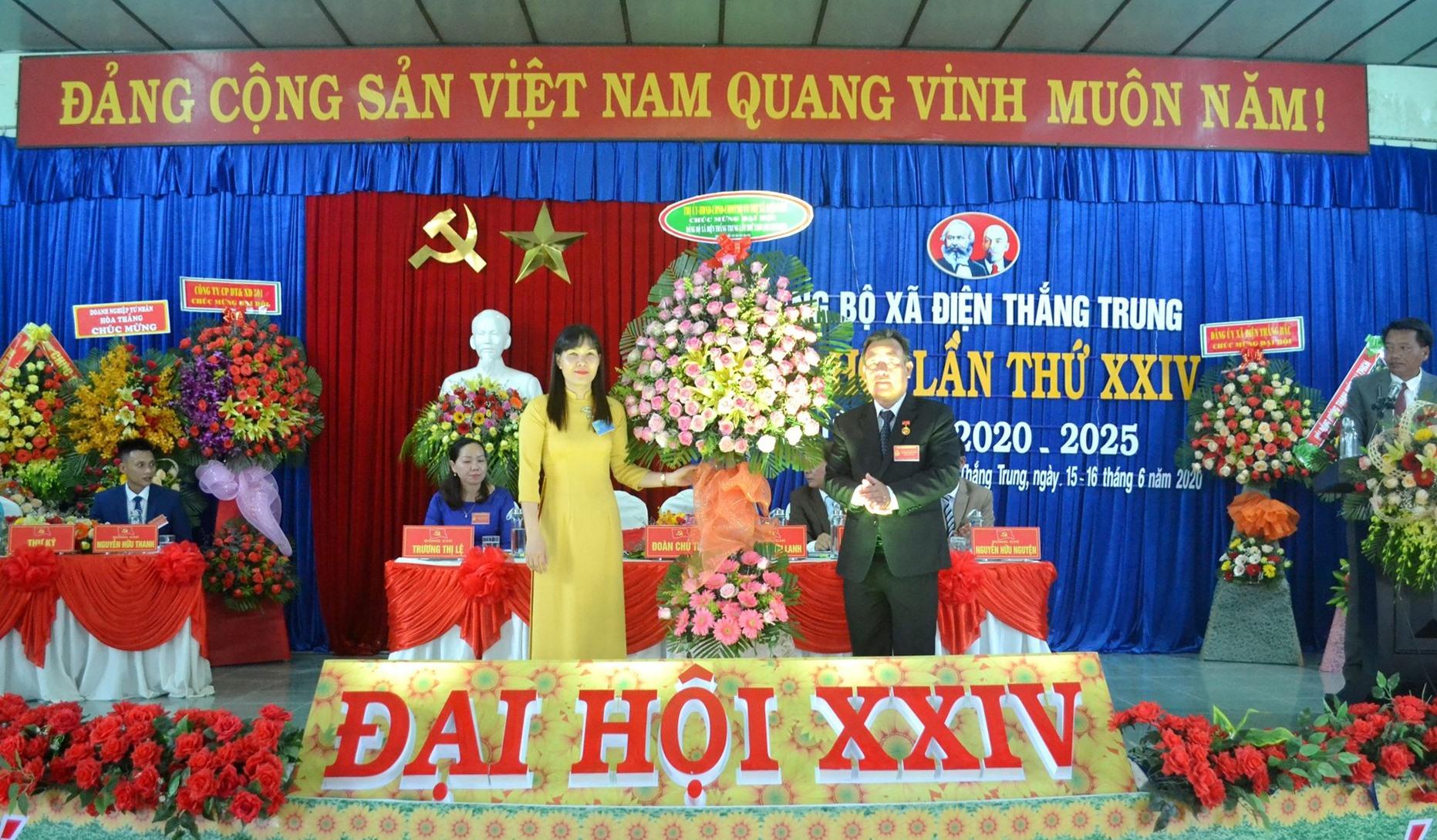Phó Bí thư Thị ủy Điện Bàn - bà Lê Thị Minh Tâm trao tặng lẵng hoa chúc mừng đại hội. Ảnh: CÔNG TÚ