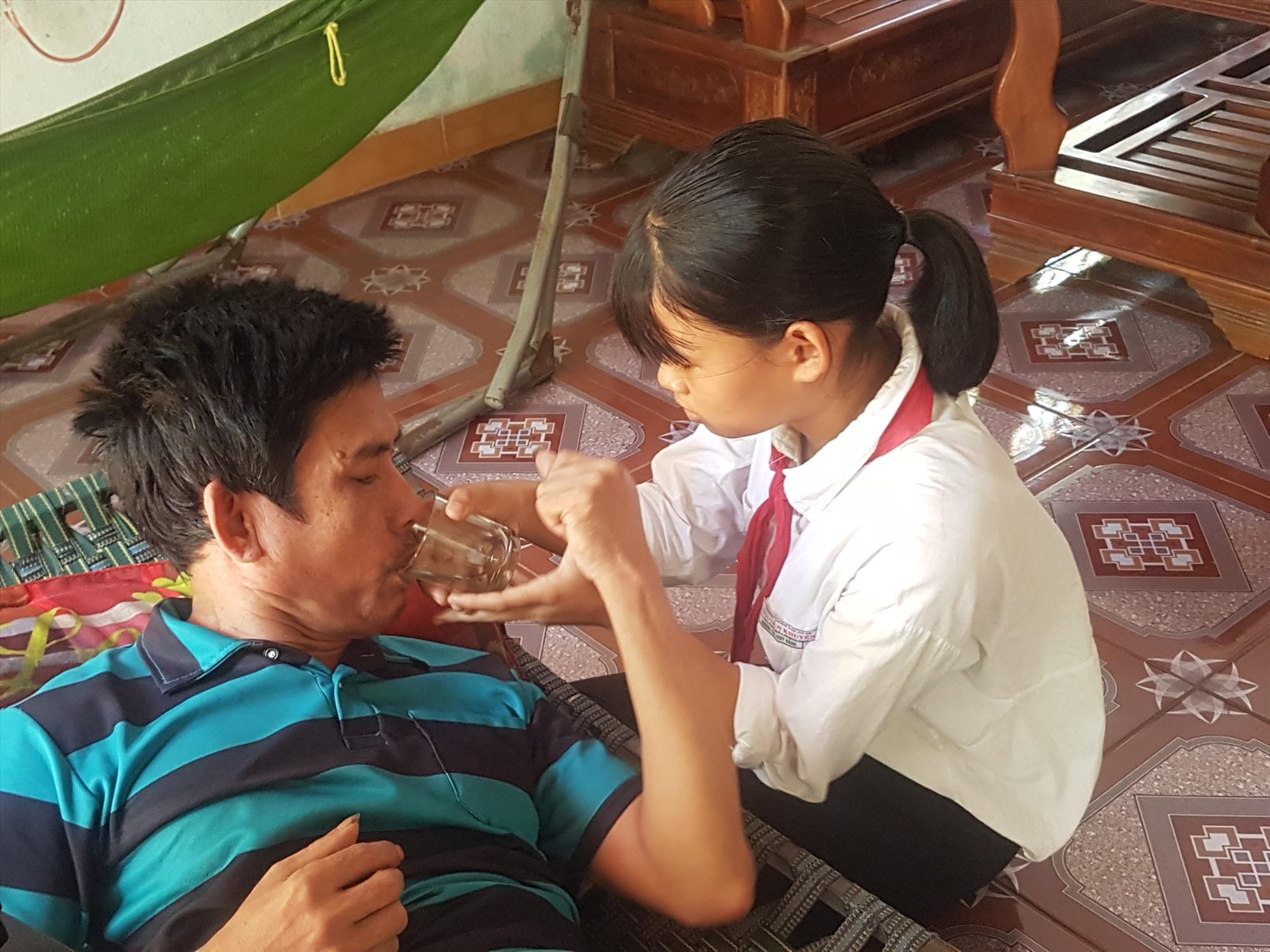 Cháu Dương Thị Thúy Hằng chăm sóc cha khi vừa đi học về. Ảnh: D.L