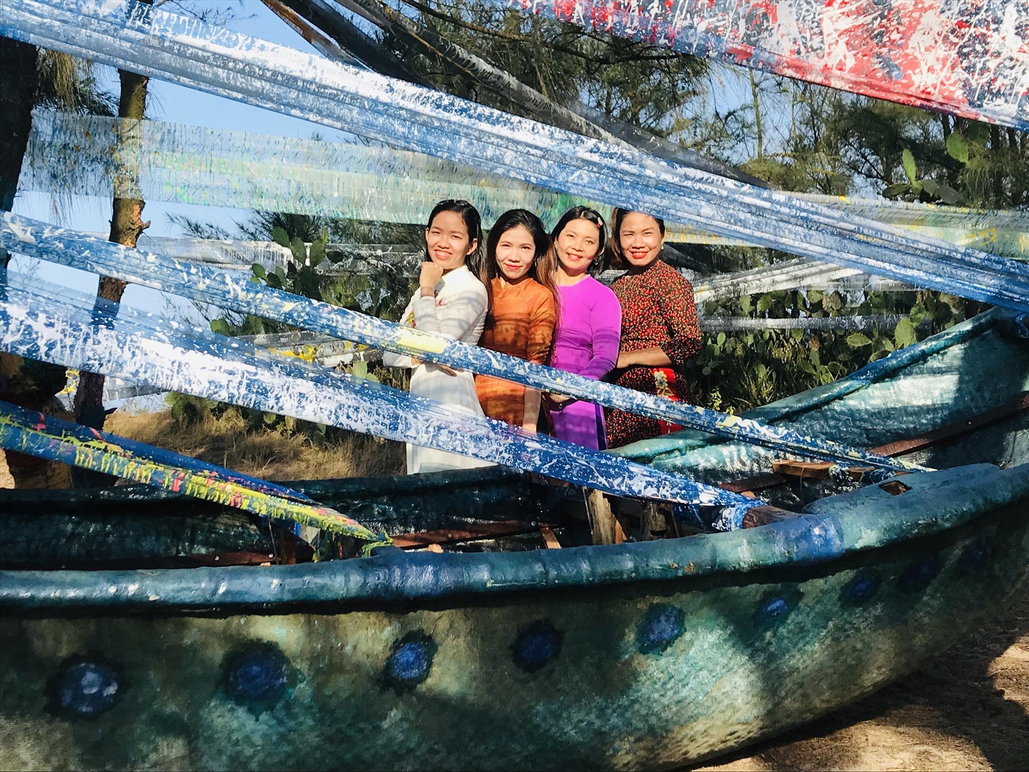 """Du khách chụp ảnh với tác phẩm """"Ra khơi"""" của họa sĩ Thu Trần. Ảnh: C.N"""