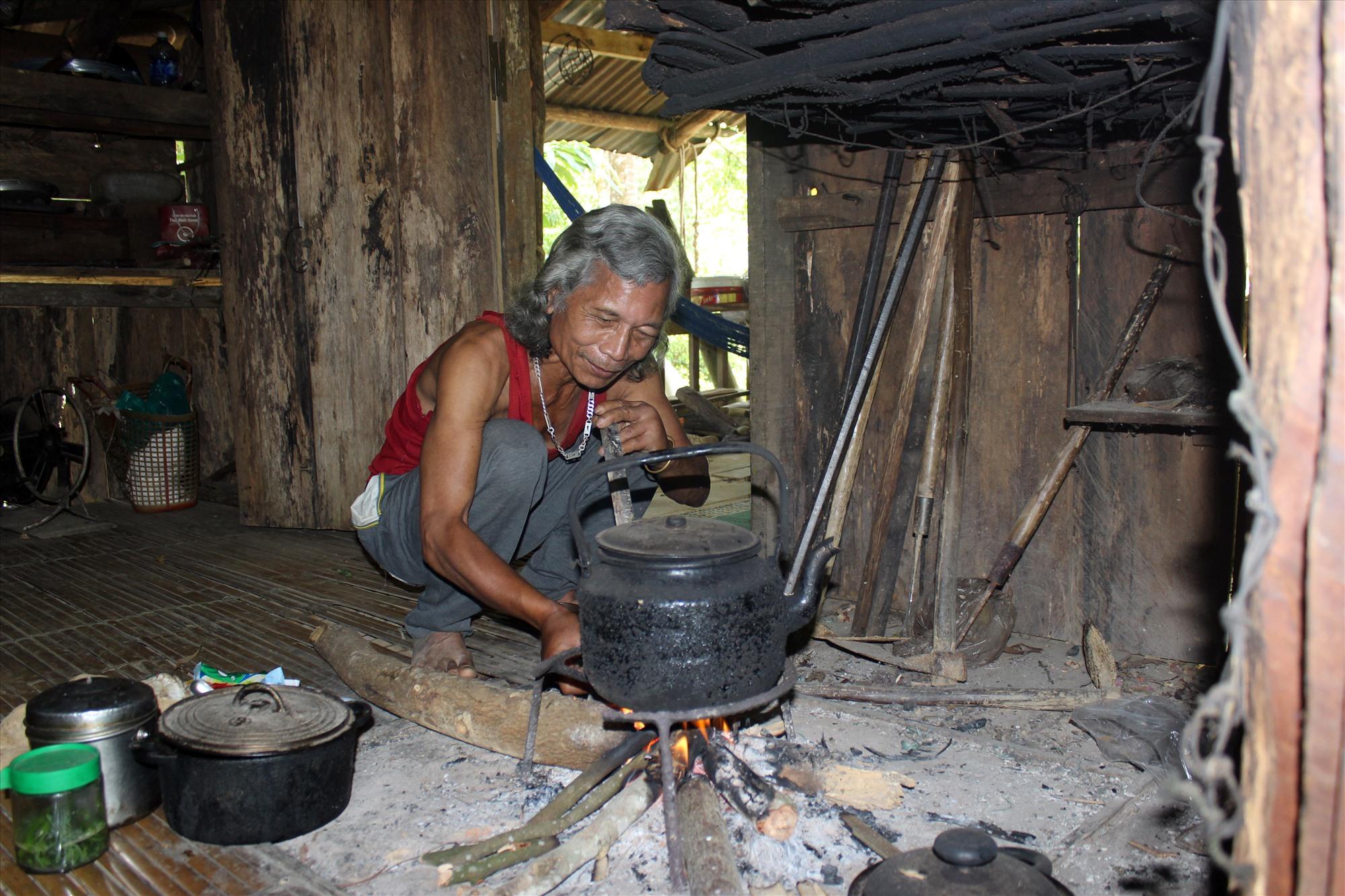 Ông Bhơriu Pố vừa hàn huyên chuyện công tác cán bộ vừa nấu nước tiếp khách dưới nhà bếp. Ảnh: BHƠRIU QUÂN