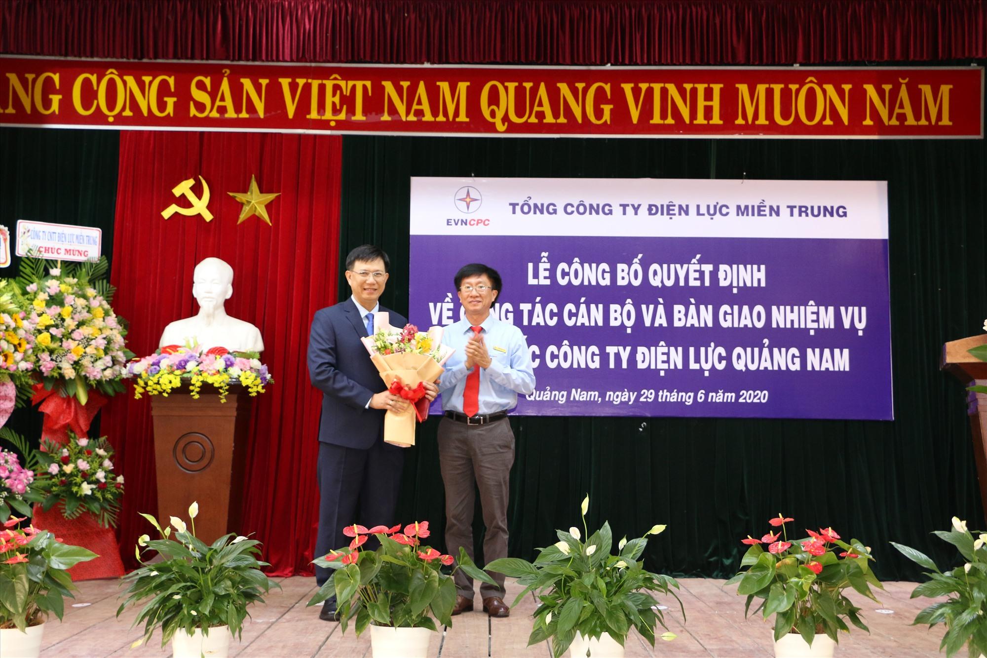 Bí thư Đảng ủy, Chủ tịch HĐTV EVNCPC Trương Thiết Hùng (phải) trao quyết định và tặng hoa cho tân Giám đốc PC Quảng Nam Nguyễn Hữu Khánh.