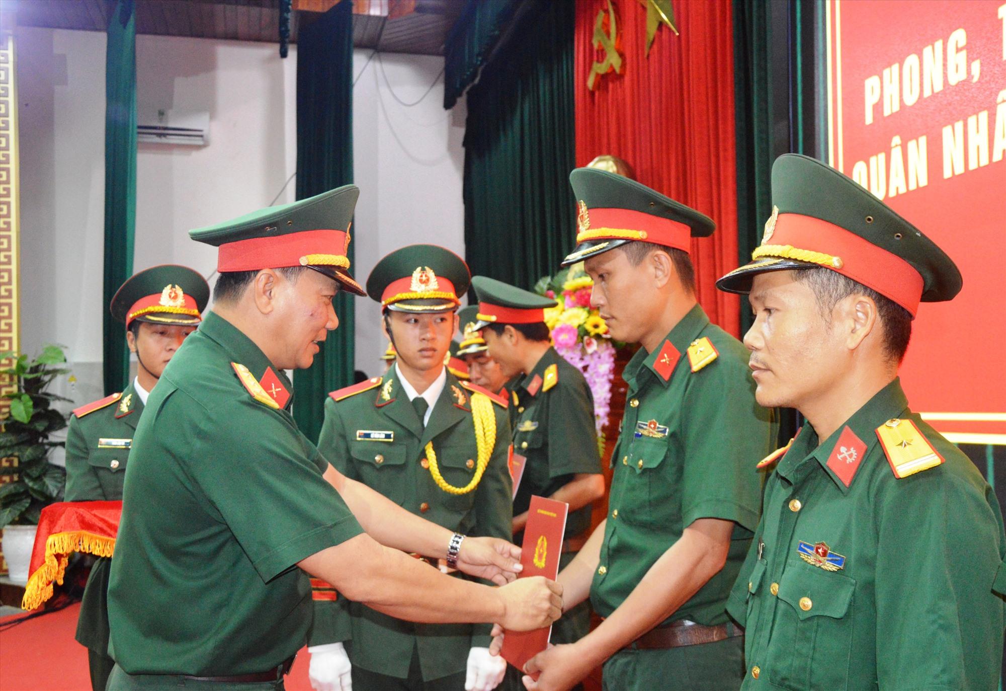 Chính ủy Bộ CHQS tỉnh trao quyết định cho cán bộ sĩ quan cấp thiếu tá.