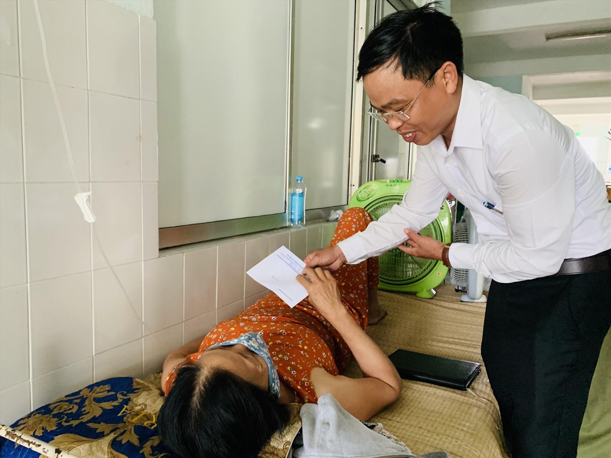 Ông Phan Văn Phẩm - Chủ tịch UBND xã Tam Thái thăm hỏi, động viên sức khỏe người dân đang nằm viện. Ảnh: PHAN VINH