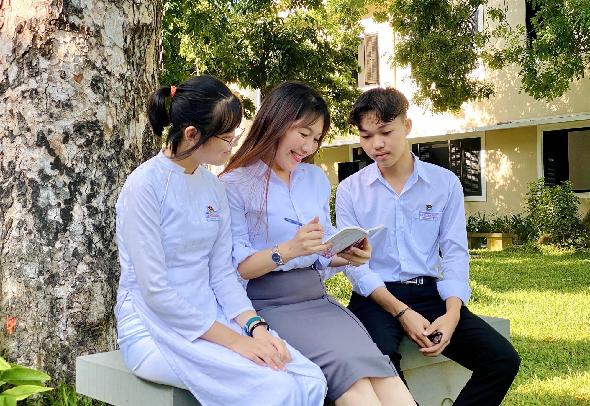Cô giáo chủ nhiệm trao đổi việc học với Quang và Ngân ngoài giờ học chính khóa. Ảnh: C.N