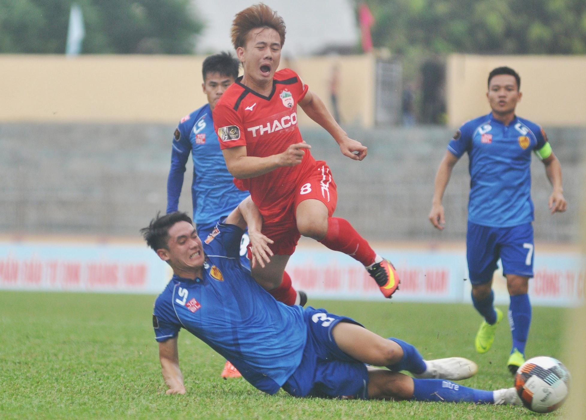 Trung vệ Tấn Sinh (áo xanh) tranh chấp quyết liệt với Minh Vương của Hoàng Anh Gia Lai ở V-League 2019. Ảnh: A.S