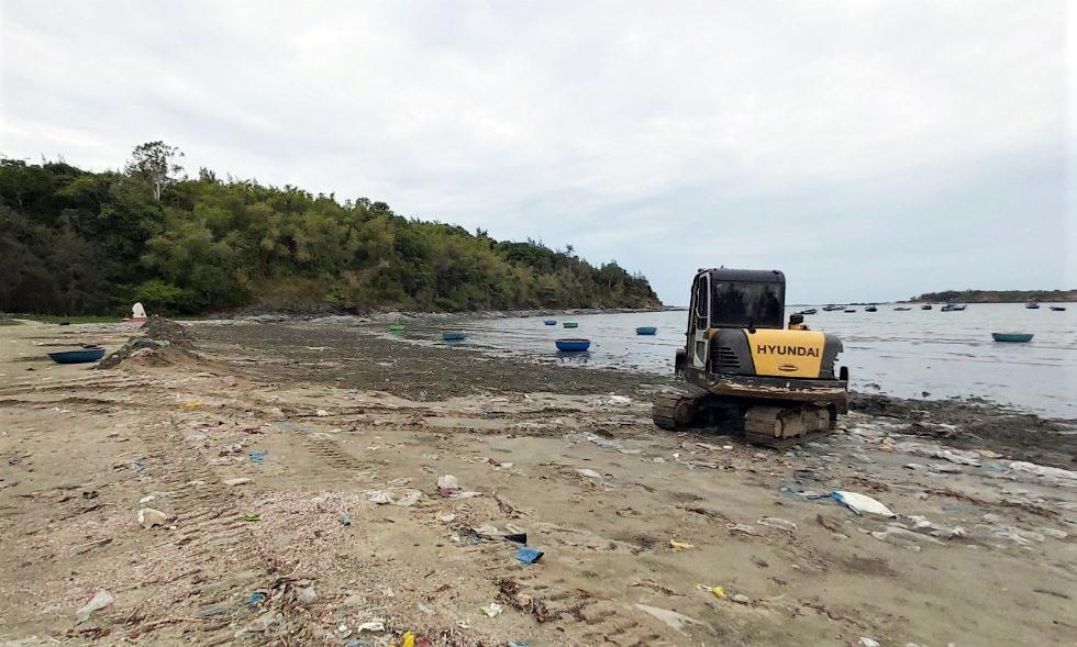 Xe múc cào xới lớp mặt để thu rác thải ở bãi Nồm (thôn Thuận An, xã Tam Hải). Ảnh: T.T