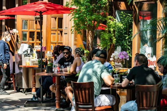 Người dân ngồi ăn bên ngoài một nhà hàng ở Manhattan, New York City, Mỹ - Ảnh: REUTERS