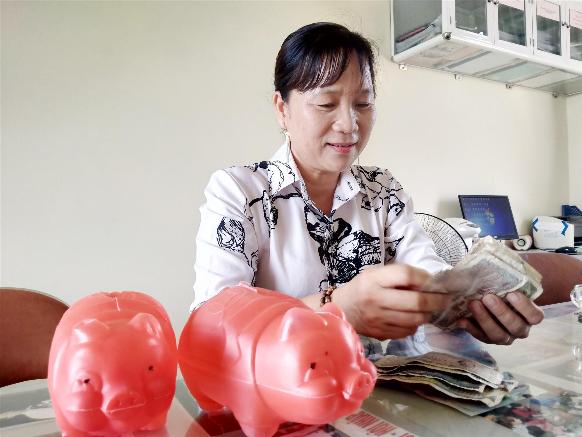 Bà Nguyễn Thị Hoa - Chủ tịch Ủy ban MTTQ Việt Nam xã Bình Minh khui heo đất góp quỹ đỡ đầu trẻ em có hoàn cảnh đặc biệt khó khăn của xã. Ảnh: N.Đ
