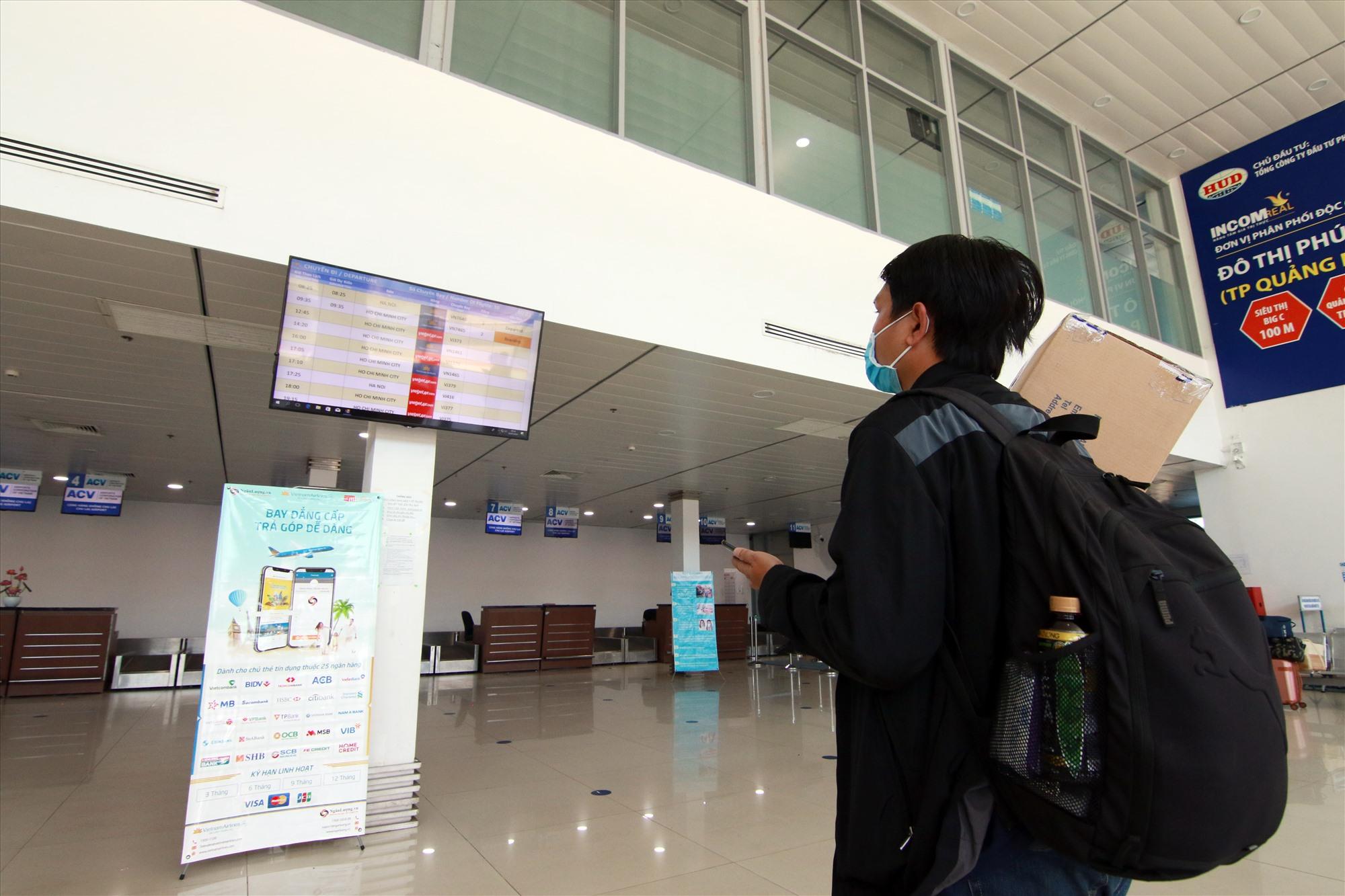 Một hành khách theo dõi lịch trình các chuyến bay tại sân bay Chu Lai vào sáng 28.7. Ảnh: T.C