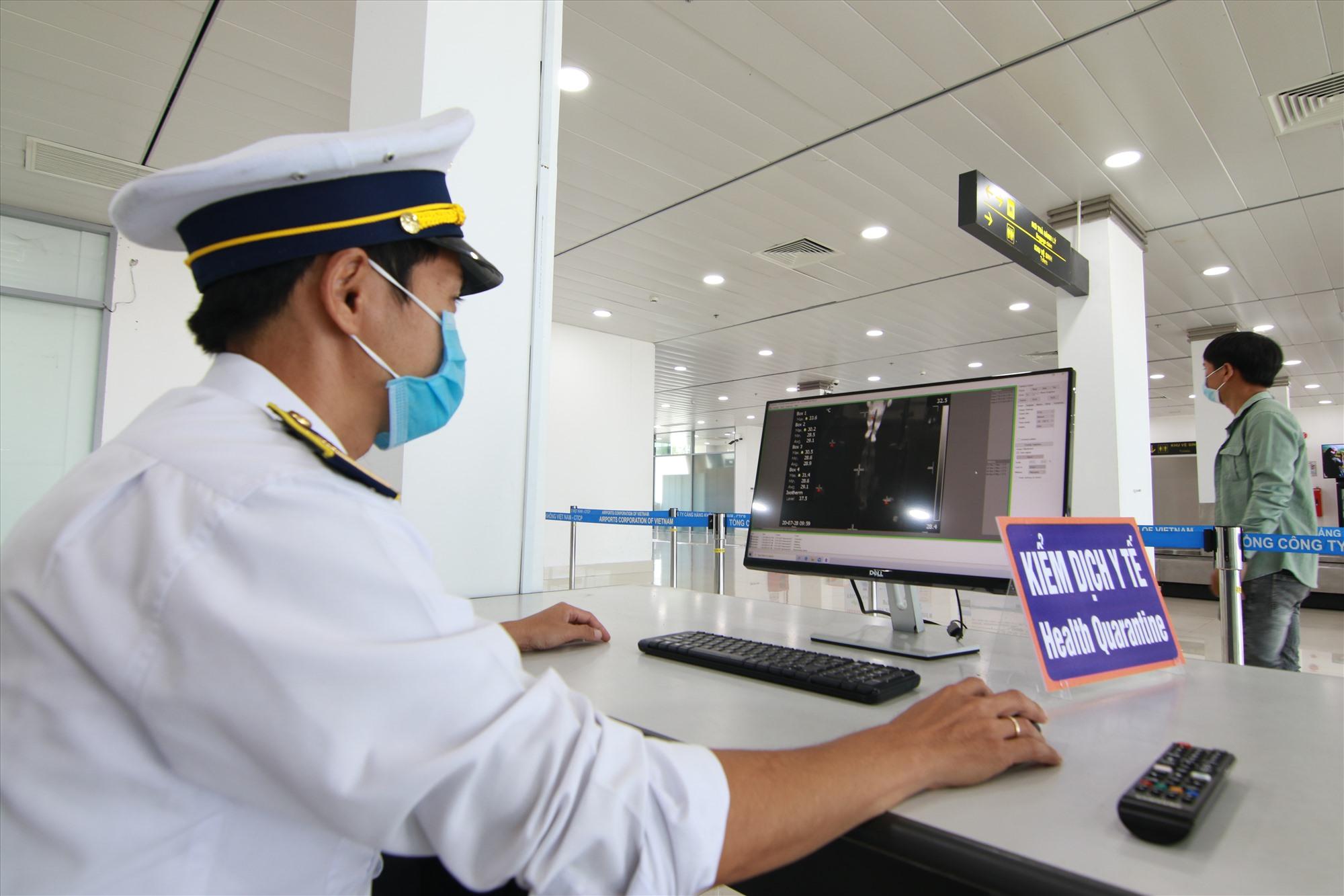 Nhân viên kiểm tra thân nhiệt hành khách bằng máy quét thân nhiệt tự động lắp đặt ở khu vực an ninh sân bay Chu Lai. Ảnh: T.C