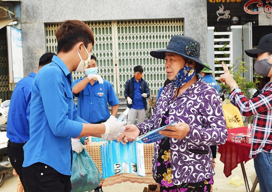 Thanh niên phát tờ rơi tuyên truyền và tặng nước sát khuẩn cho người dân. Ảnh: T.N