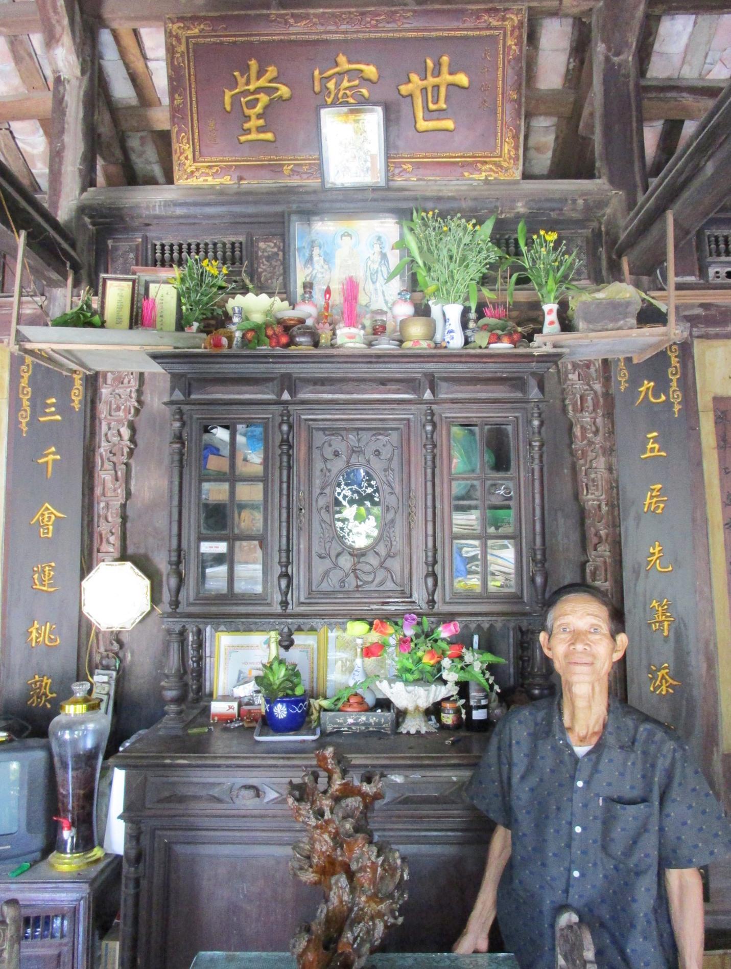 Ông Phạm Tấn Tuấn trước bàn thờ nhà cổ có lưu thơ Hà Đình. Ảnh: PHÚ BÌNH