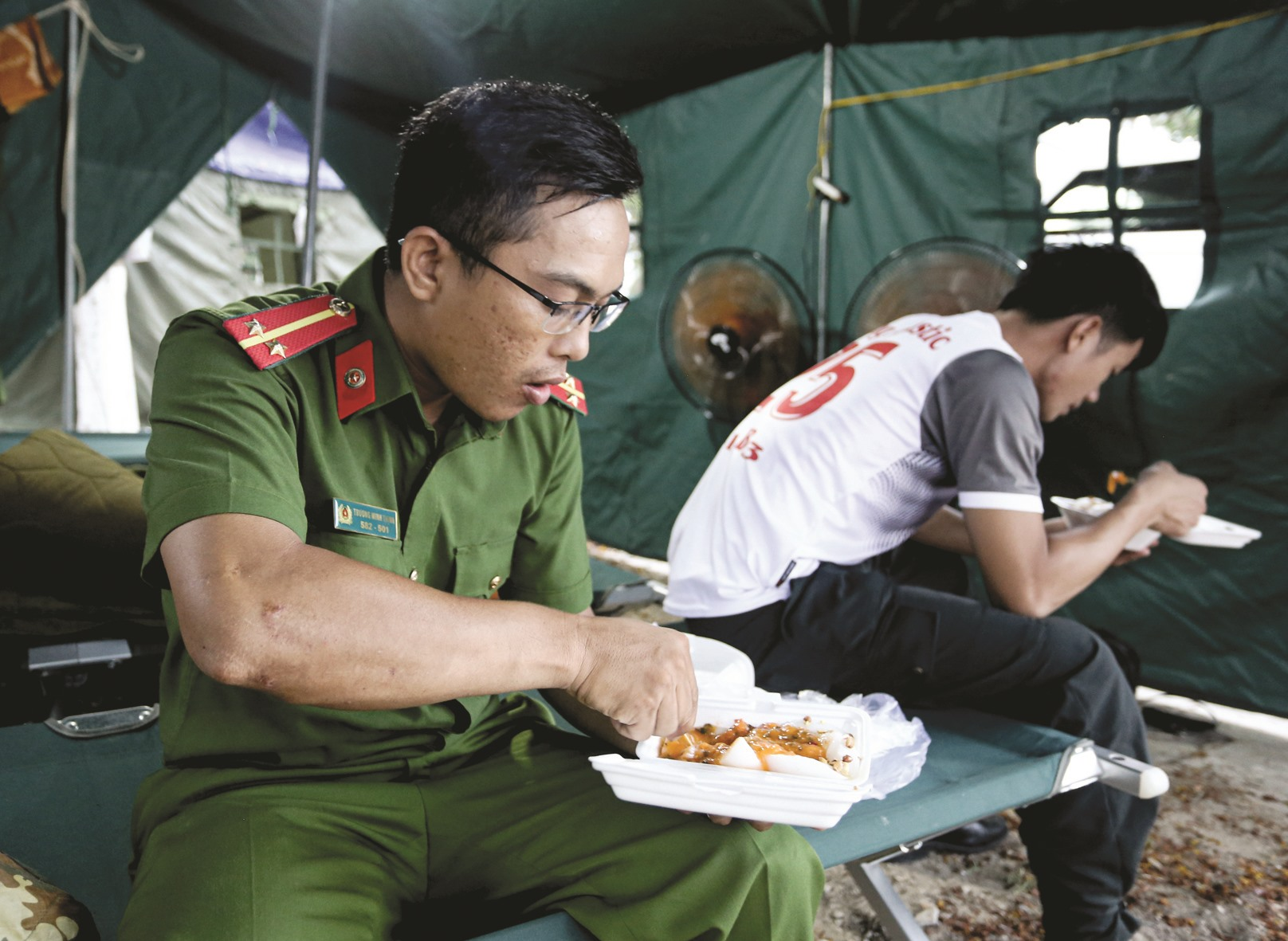 Bữa ăn vội vã trong lán trại của các chiến sĩ Cảnh sát cơ động (Công an tỉnh).Ảnh: SƠN THỦY
