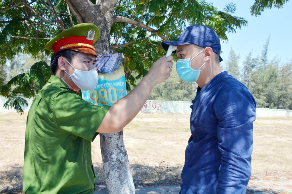 Lực lượng công an đo thân nhiệt cho người dân tại chốt kiểm dịch. Ảnh: X.M