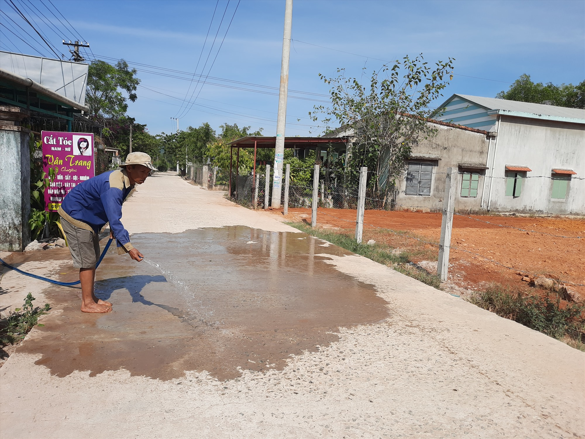 Người dân liên tục tưới nước để hạn chế tình trạng bụi bặm mù mịt xuất hiện sau khi đường đi vào hoạt động. Ảnh: HỒ QUÂN
