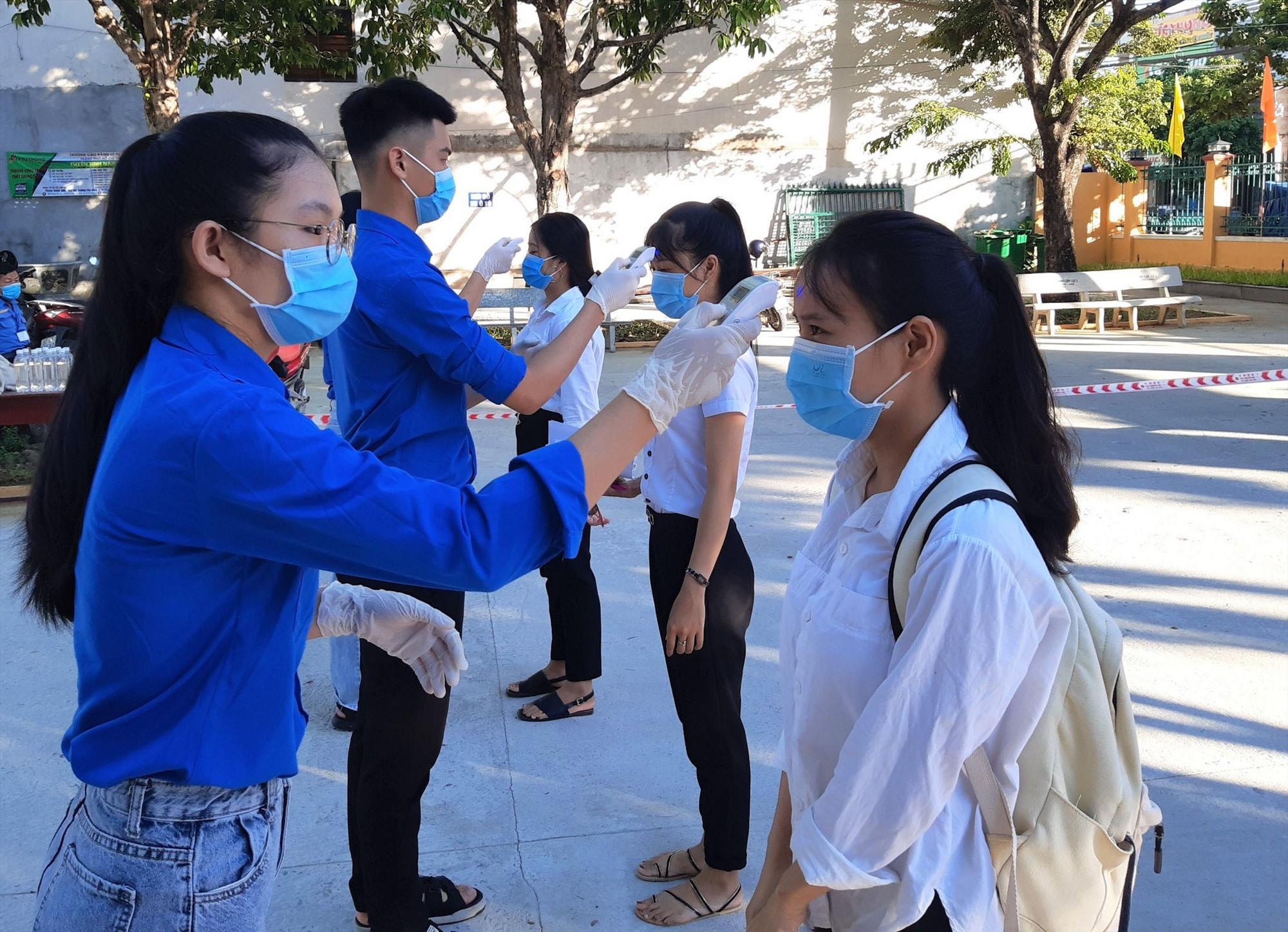 Thanh niên tình nguyện đo thân nhiệt cho thí sinh TP.Tam Kỳ trước khi bước vào phòng thi. Ảnh: VINH ANH
