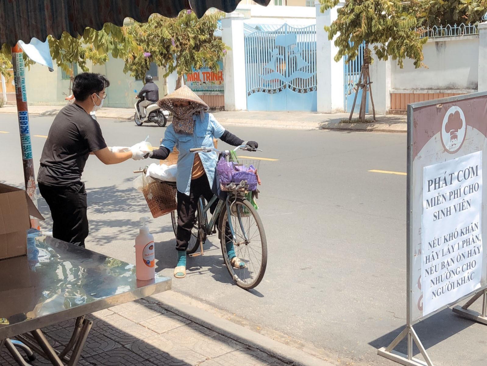 Sinh viên Trường Đại học Duy Tân Đà Nẵng trao phần cơm hỗ trợ người lao động nghèo. Ảnh: Q.T