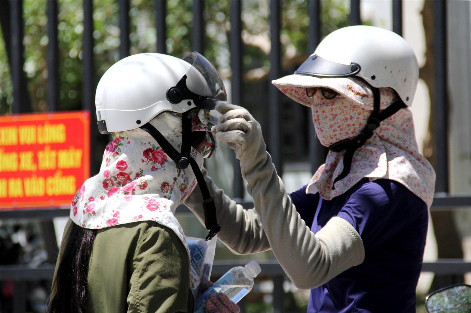 Một phụ huynh trùm kín mặt, đội giúp con mũ bảo hiểm ngay tại cổng trường. Ảnh: A.N