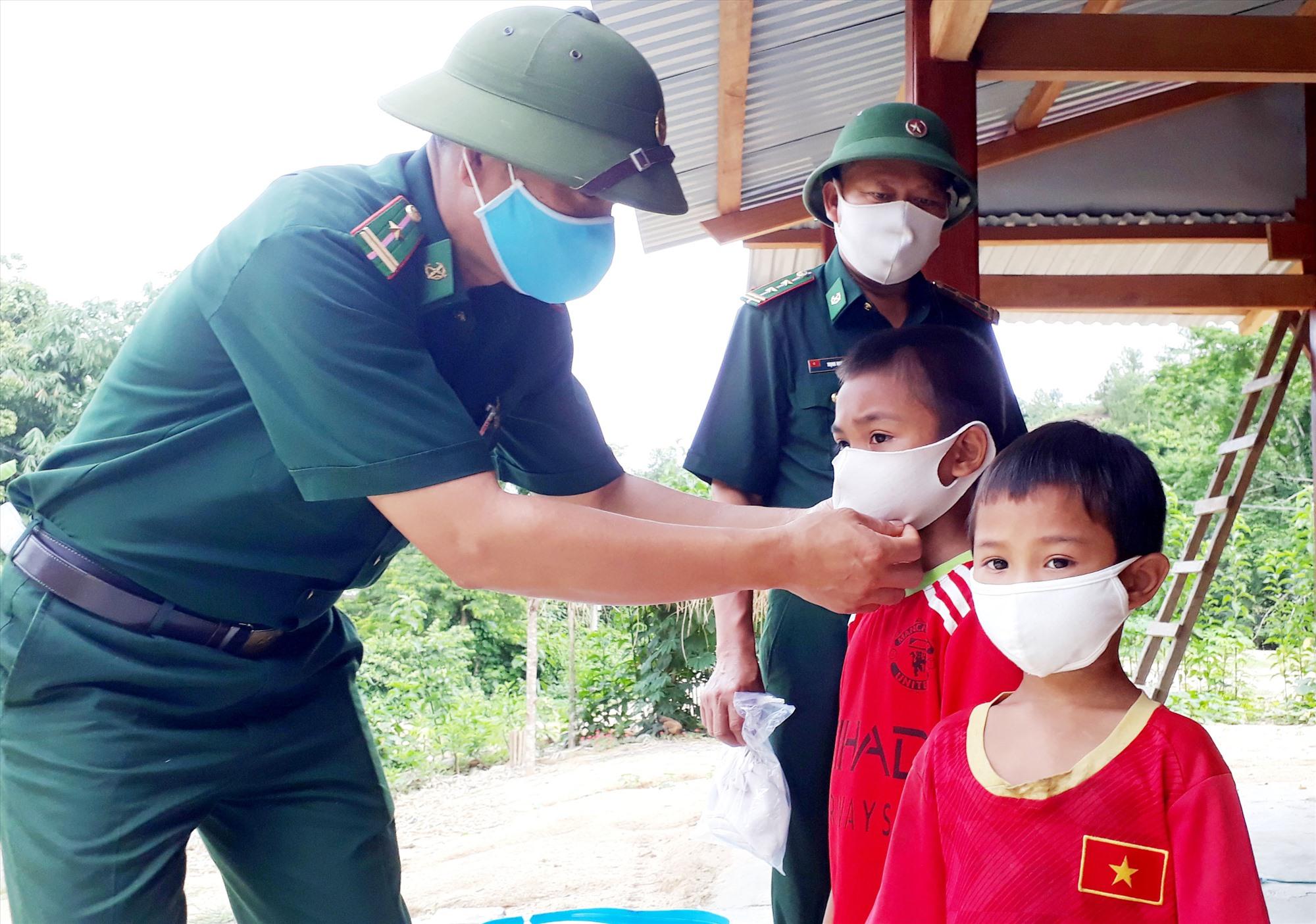 Các chiến sĩ Đồn Biên phòng Đắc Pring hướng dẫn trẻ em biên giới đeo khẩu trang đúng cách phòng dịch Covid-19. Ảnh: Đ.N
