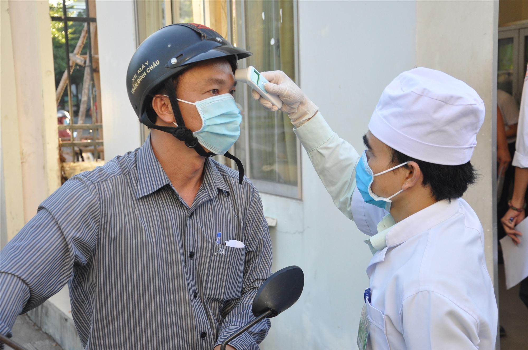 Nhân viên y tế làm việc hết công suất tại các  buổi thi để đo thân nhiệt cán bộ coi thi, TS. Ảnh: X.P