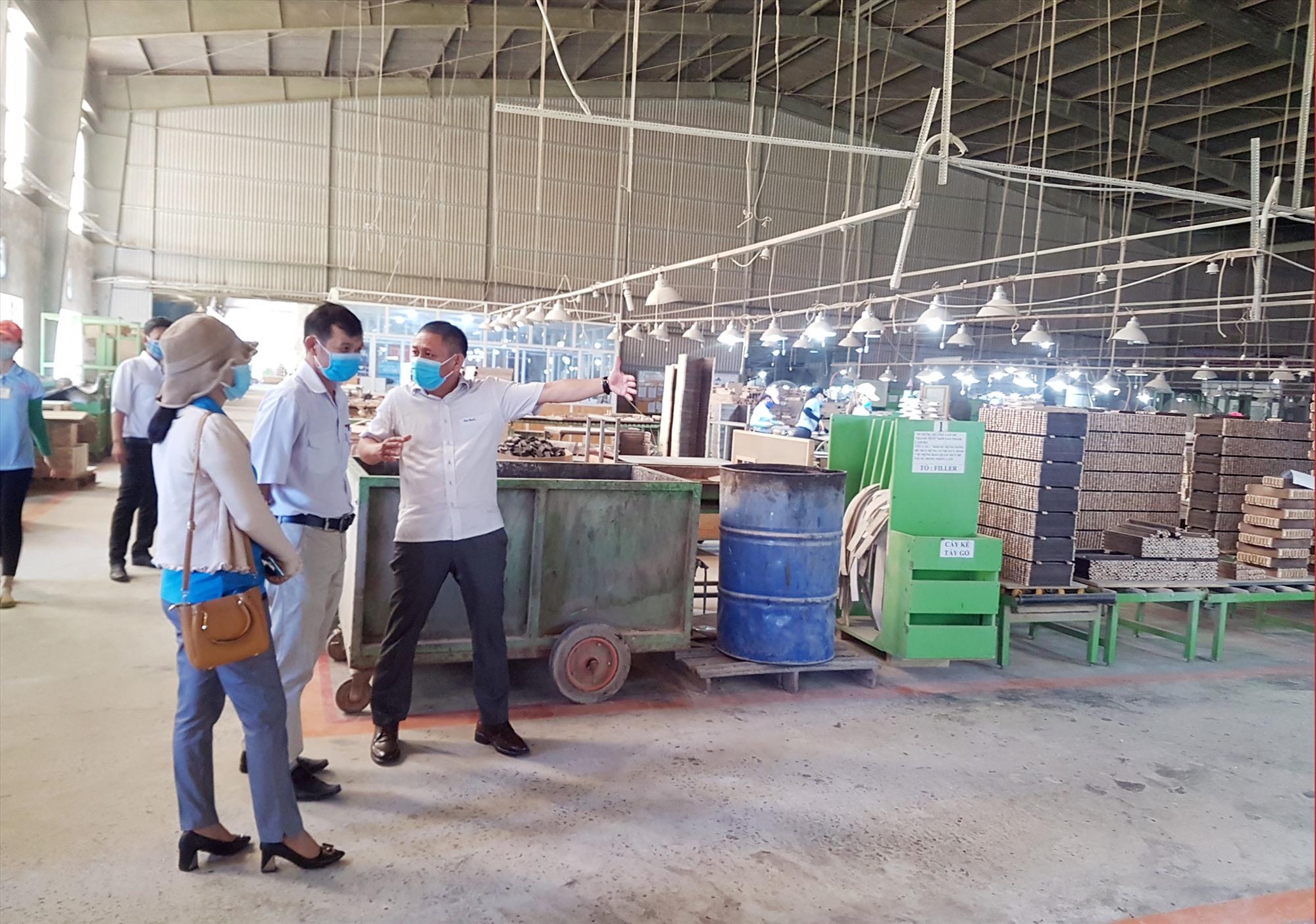 Đoàn kiểm tra nhắc nhở chủ doanh nghiệp về những quy định phòng chống dịch cần khắc phục tại nhà máy sản xuất. Ảnh: D.L