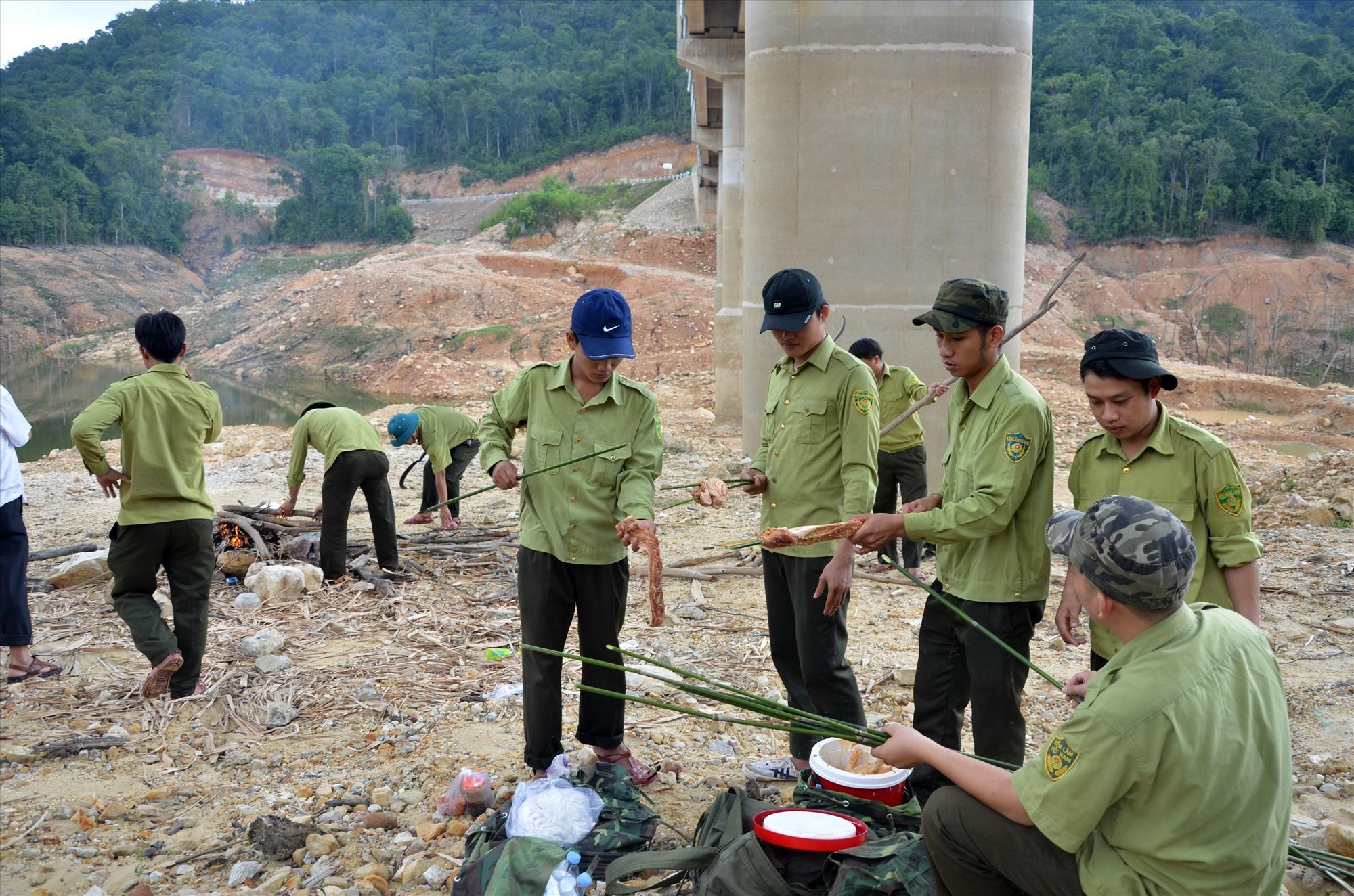 Lực lượng bảo vệ rừng chuyên trách của Ban Quản lý Khu bảo tồn loài và sinh cảnh voi Nông Sơn chuẩn bị bữa ăn trưa khi tuần tra ở lưu vực thủy điện Khe Diên. Ảnh: H.P
