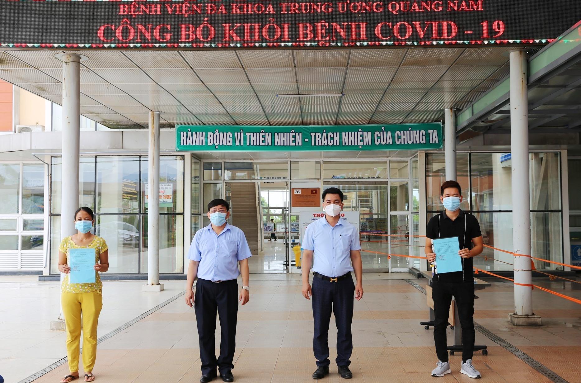 Lãnh đạo Bệnh viện Đa khoa Trung ương Quảng Nam trao giấy xác nhận hoàn thành điều trị Covid-19 và thực hiện các thủ tục xuất viện cho hai bệnh nhân 716, 719. Ảnh: LÊ PHƯƠNG THẢO
