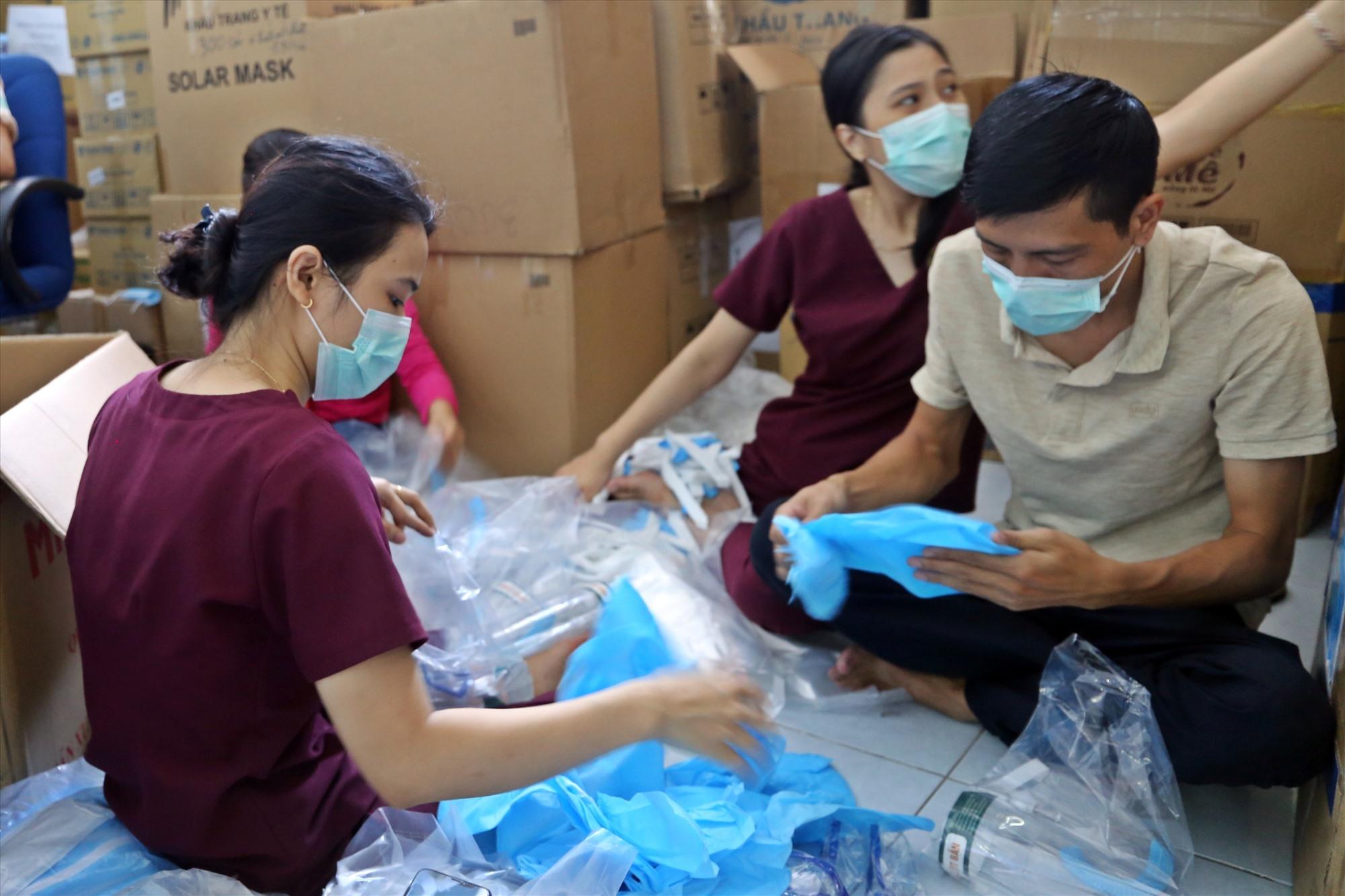Các y bác sĩ, nhân viên của Bệnh viện Đa khoa Trung ương Quảng Nam tranh thủ buổi tối để chuẩn bị các trang bị bảo hộ cho đội ngũ điều trị bệnh nhân Covid-19. Ảnh: THẢO ĐẠO