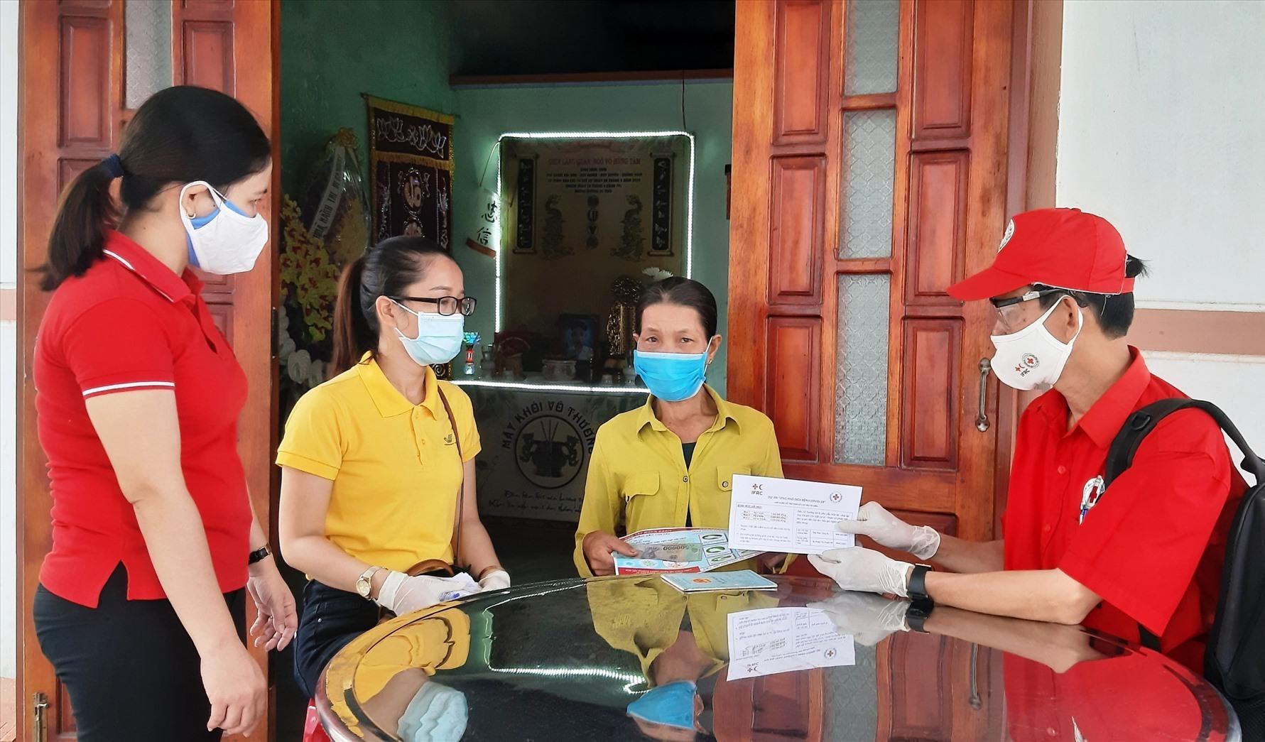 Đại diện lãnh đạo Hội Chữ thập đỏ tỉnh đến tận nhà trao tiền hỗ trợ người dân xã Duy Nghĩa vào sáng nay 14.8. Ảnh: T.P