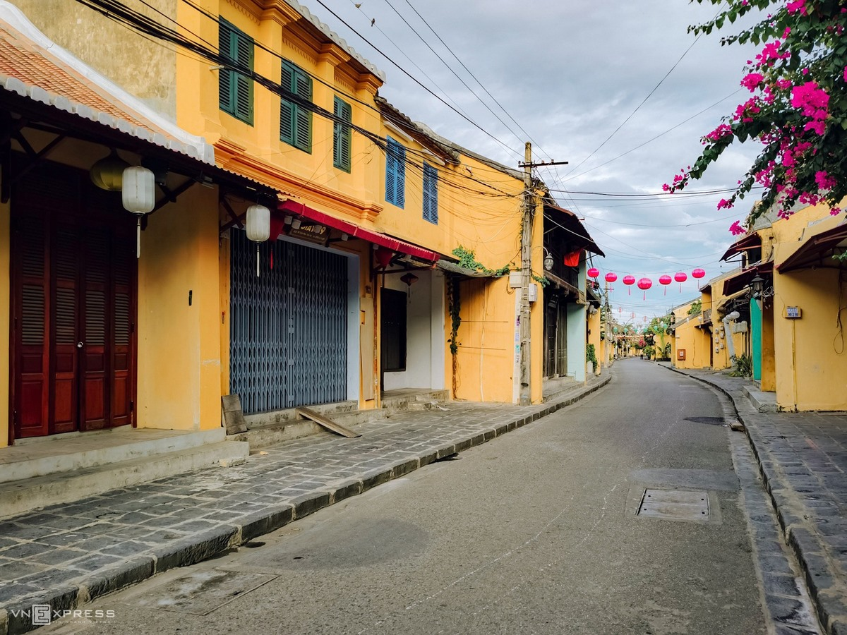 Deserted Hoi An with yellow walls and pink Bougainvillea flowers
