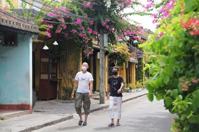 Foreign visitors in Hoi An wear face masks to prevent the spread of COVID-19. Photo: VOV