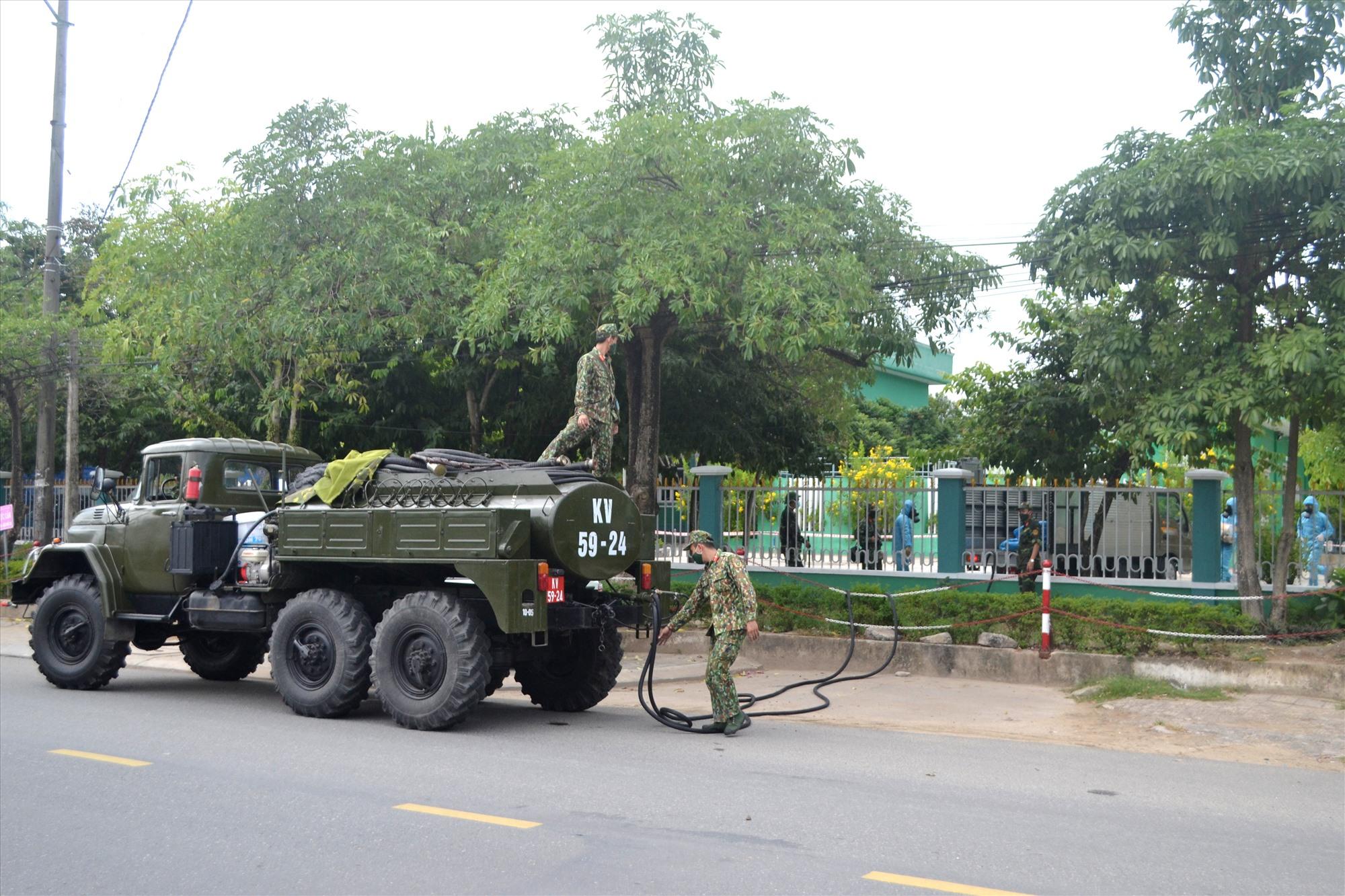 Tiếp thêm dung dịch cho các chiến sĩ triển khai phun tại các vị trí mà ô tô không thể tiếp cận. Ảnh: CT