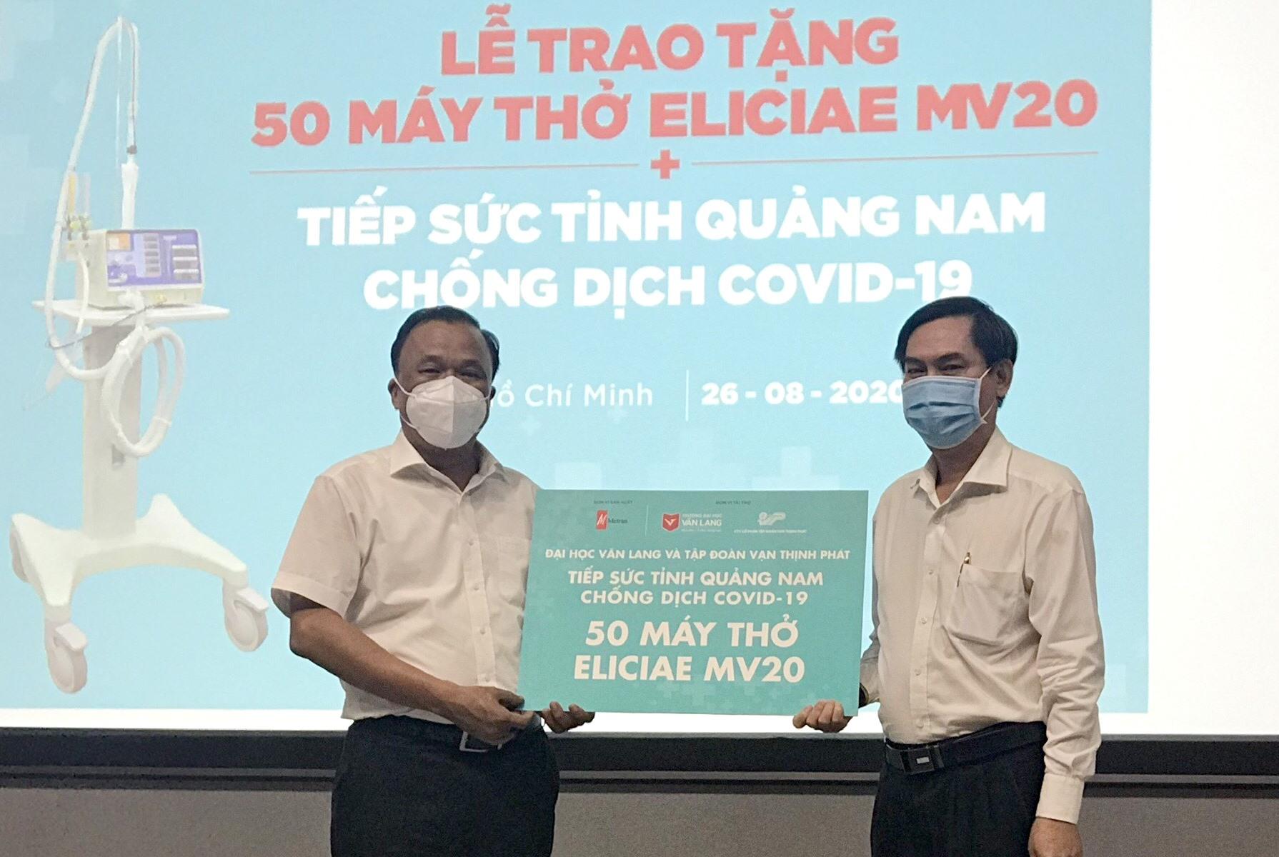 Ông Mai Văn Mười - Phó Giám đốc Sở Y tế (bên trái) tiếp nhận máy thở từ lãnh đạo Trường Đại học Văn Lang. Ảnh: THÙY AN