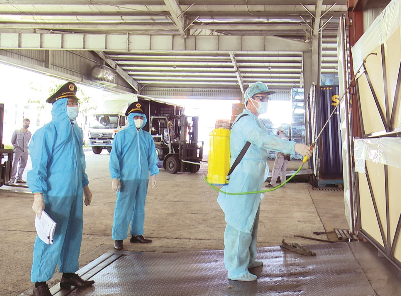 Spraying disinfectant on containers