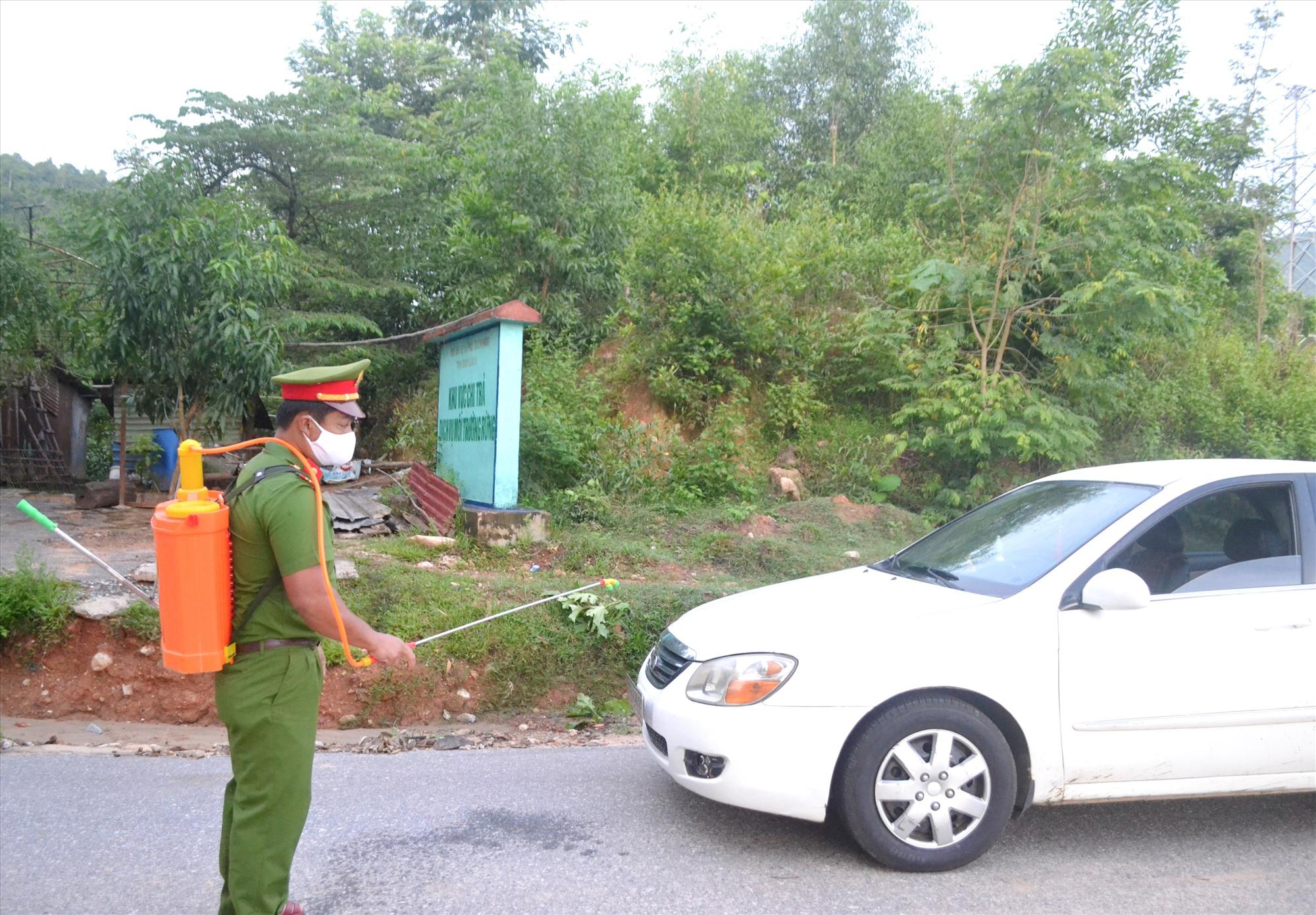 Cán bộ Công an Đông Giang phun khử trùng phương tiện qua chốt chặn kiểm soát dịch Covid-19 trên đường Hồ Chí Minh. Ảnh: C.T